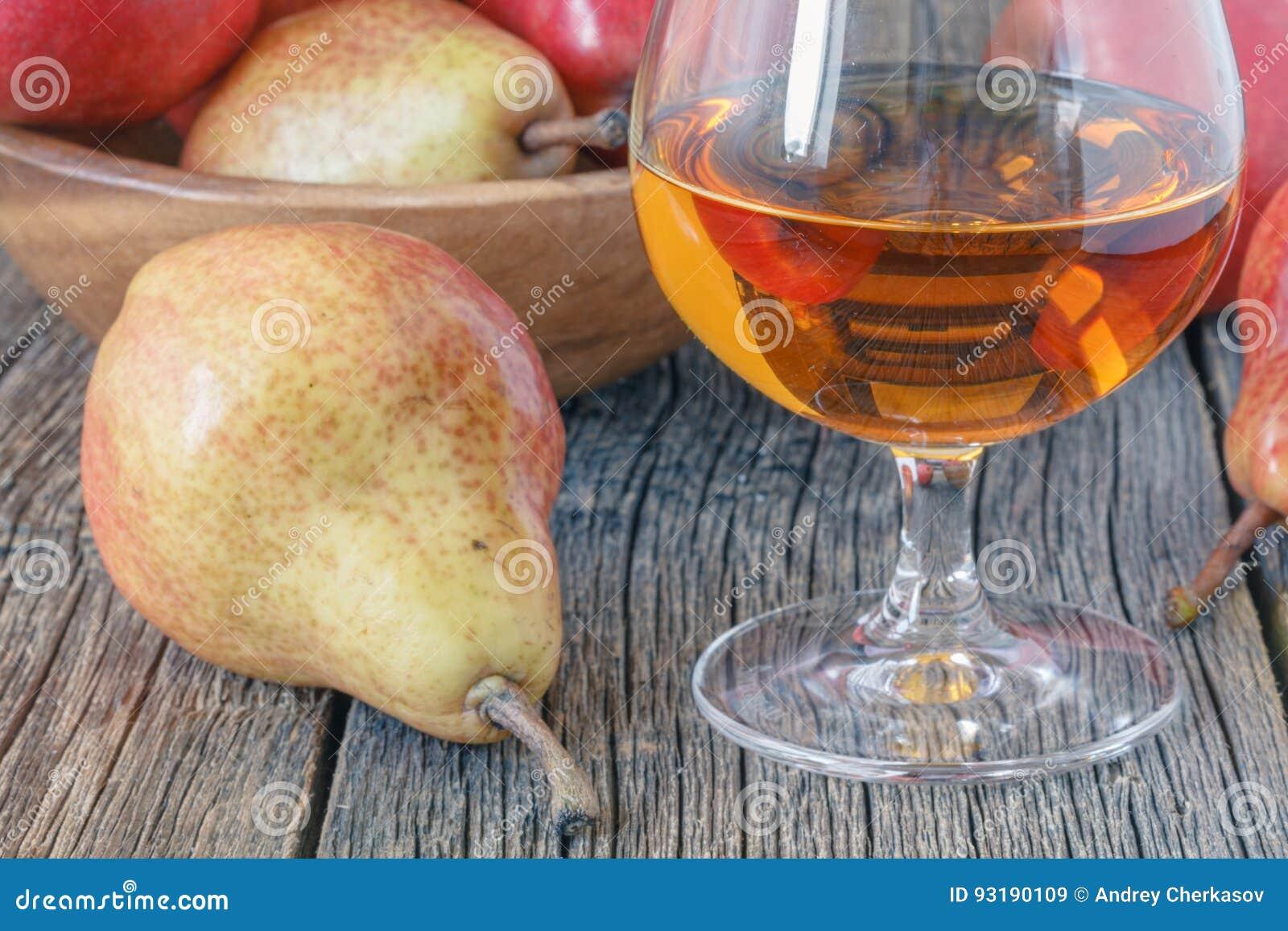 Μπουκάλι του κονιάκ αχλαδιών aguardiente και του φρέσκου αχλαδιού στο αγροτικό σκοτάδι