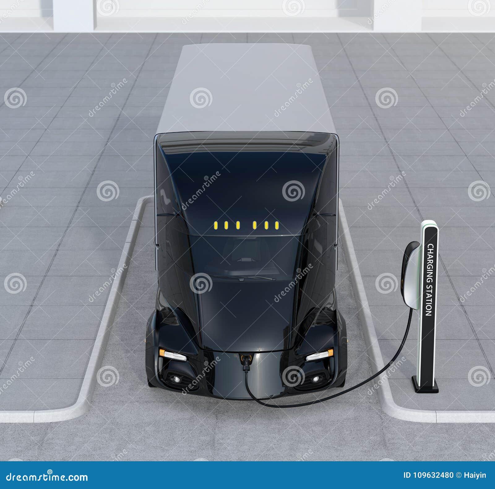 Μπροστινή άποψη της μόνος-οδήγησης του ηλεκτρικού φορτηγού που χρεώνει στο σταθμό χρέωσης