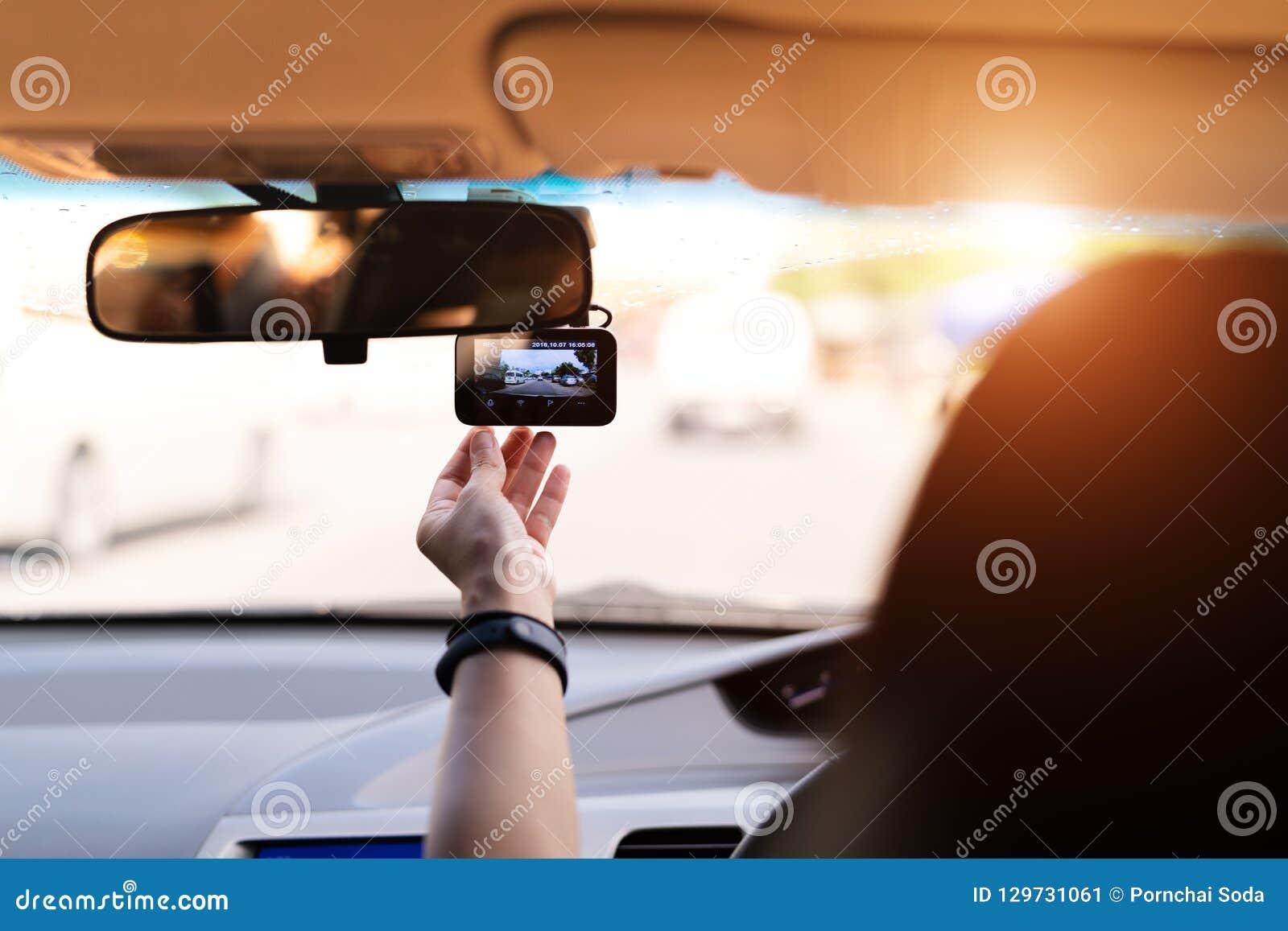 Μπροστινό όργανο καταγραφής αυτοκινήτων καμερών, καθορισμένο βίντεο εγγραφής γυναικών δίπλα σε έναν οπισθοσκόπο καθρέφτη
