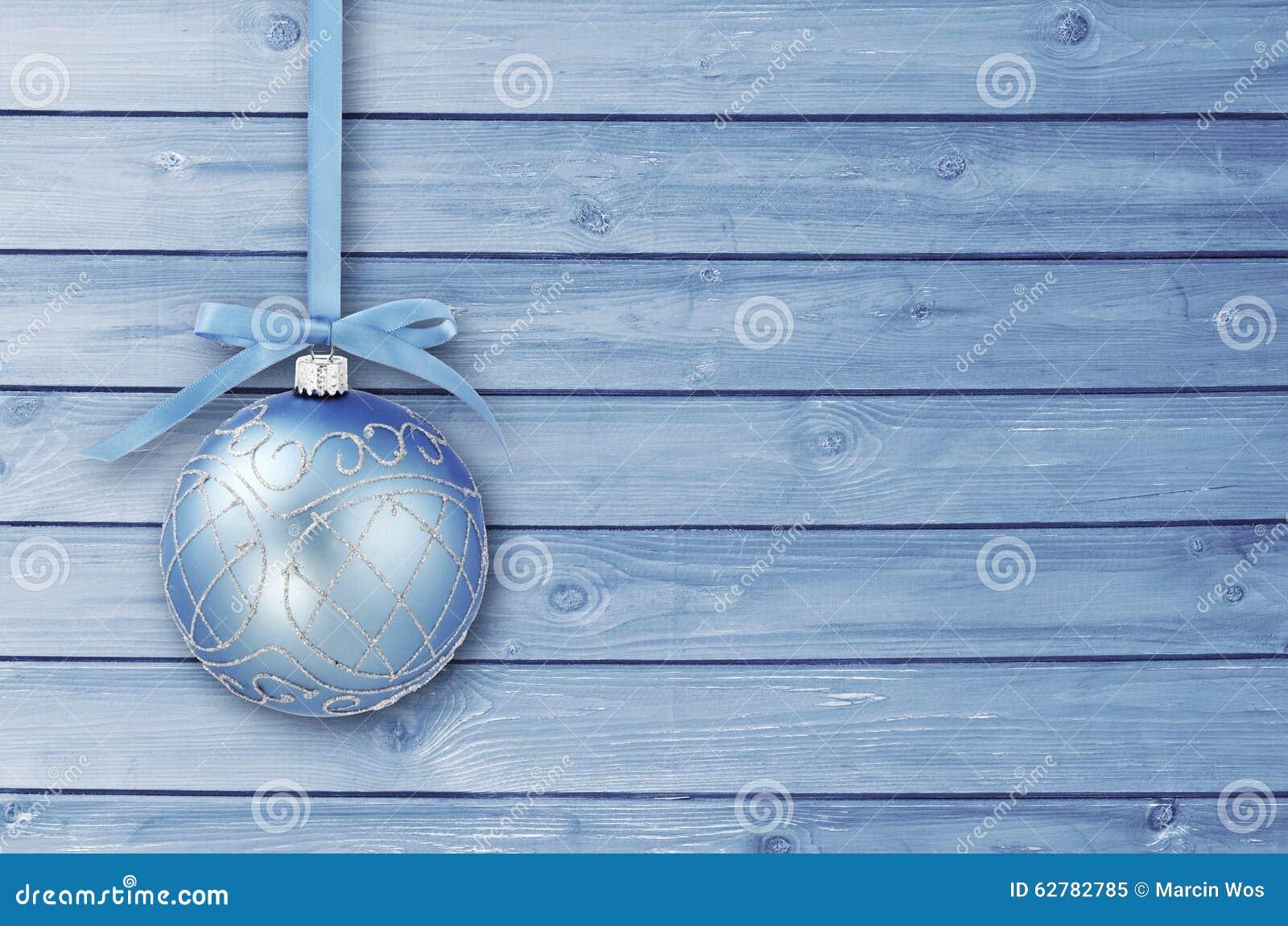 Μπλε μπιχλιμπίδια Χριστουγέννων με τη σγουρή κορδέλλα σε έναν μπλε ξύλινο πίνακα με το διάστημα αντιγράφων Χριστούγεννα καρτών απ