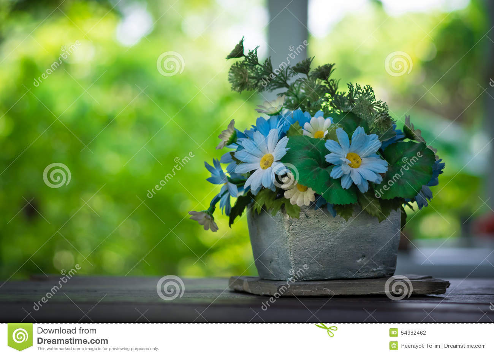 Μπλε λουλούδια στο βάζο πετρών