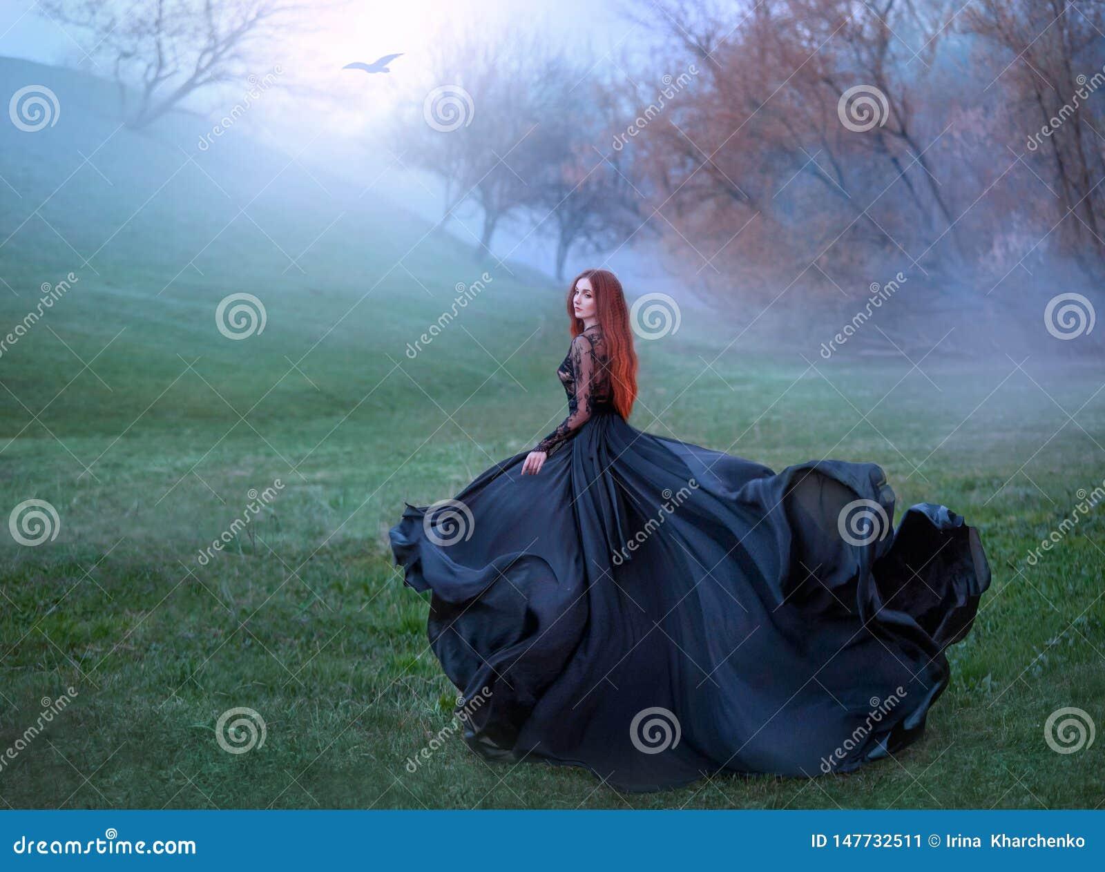 Μυστήριο κορίτσι με τα κόκκινα τρεξίματα τρίχας από το δάσος στο πανέμορφο βασιλικό φόρεμα δαντελλών με το πετώντας ελαφρύ μακρύ