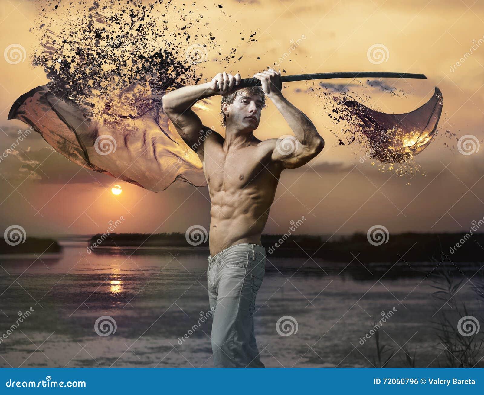 Μυϊκός όμορφος τύπος με το ξίφος στο ηλιοβασίλεμα