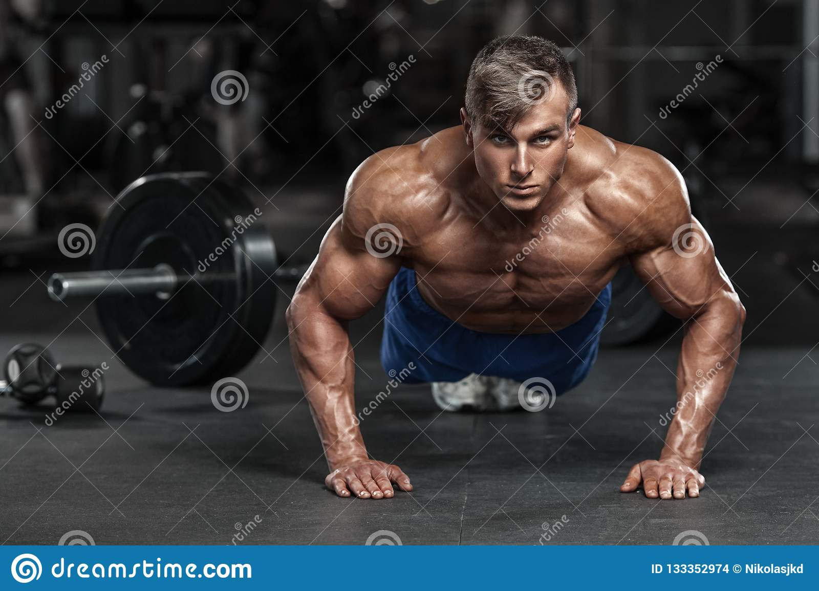 Μυϊκό άτομο που επιλύει στη γυμναστική που κάνει ώθηση-UPS τις ασκήσεις, ισχυρά αρσενικά γυμνά ABS κορμών
