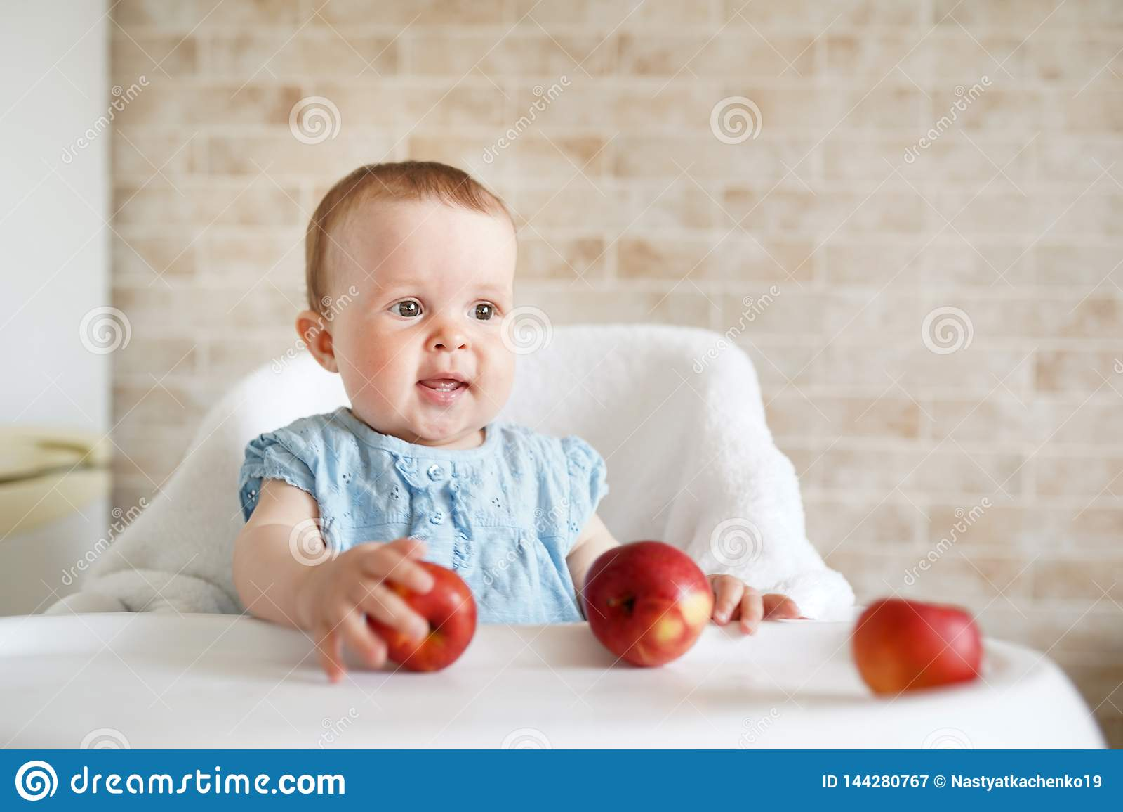 Μωρό που τρώει τα φρούτα Μικρό κορίτσι που δαγκώνει την κίτρινη συνεδρίαση μήλων στην άσπρη υψηλή καρέκλα στην ηλιόλουστη κουζίνα