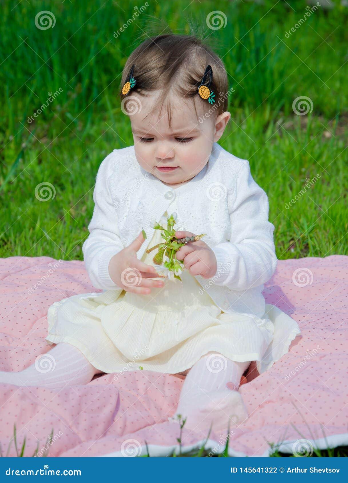 Μωρό στα φωτεινά ενδύματα σε ένα ρόδινο καρό στην πράσινη χλόη στο πάρκο