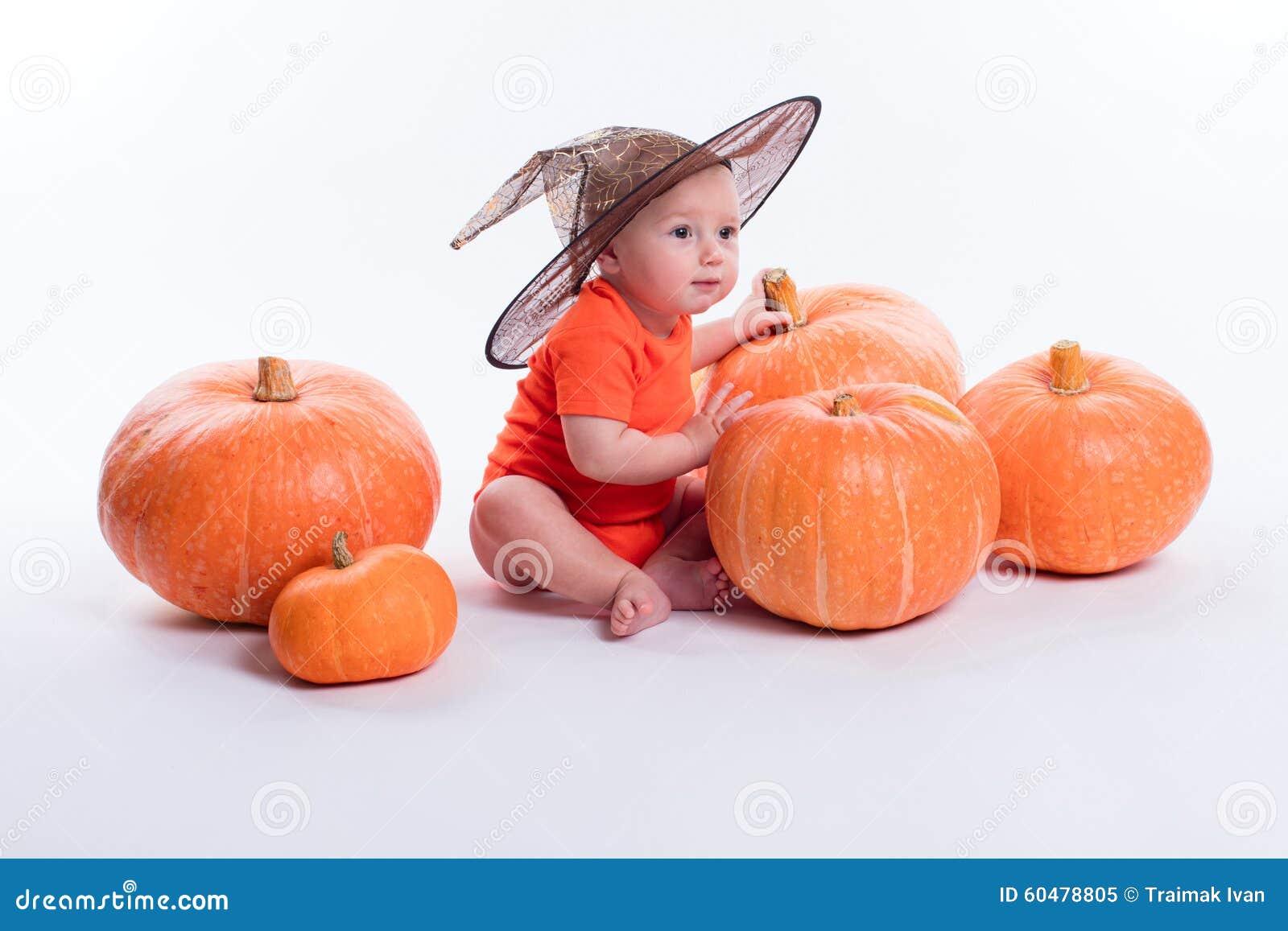 Μωρό στην πορτοκαλιά μπλούζα σε μια άσπρη συνεδρίαση υποβάθρου σε ένα witche