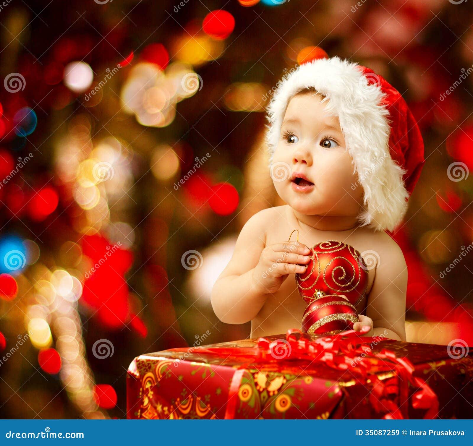 Μωρό Χριστουγέννων στο καπέλο santa κοντά στο κόκκινο παρόν κιβώτιο δώρων