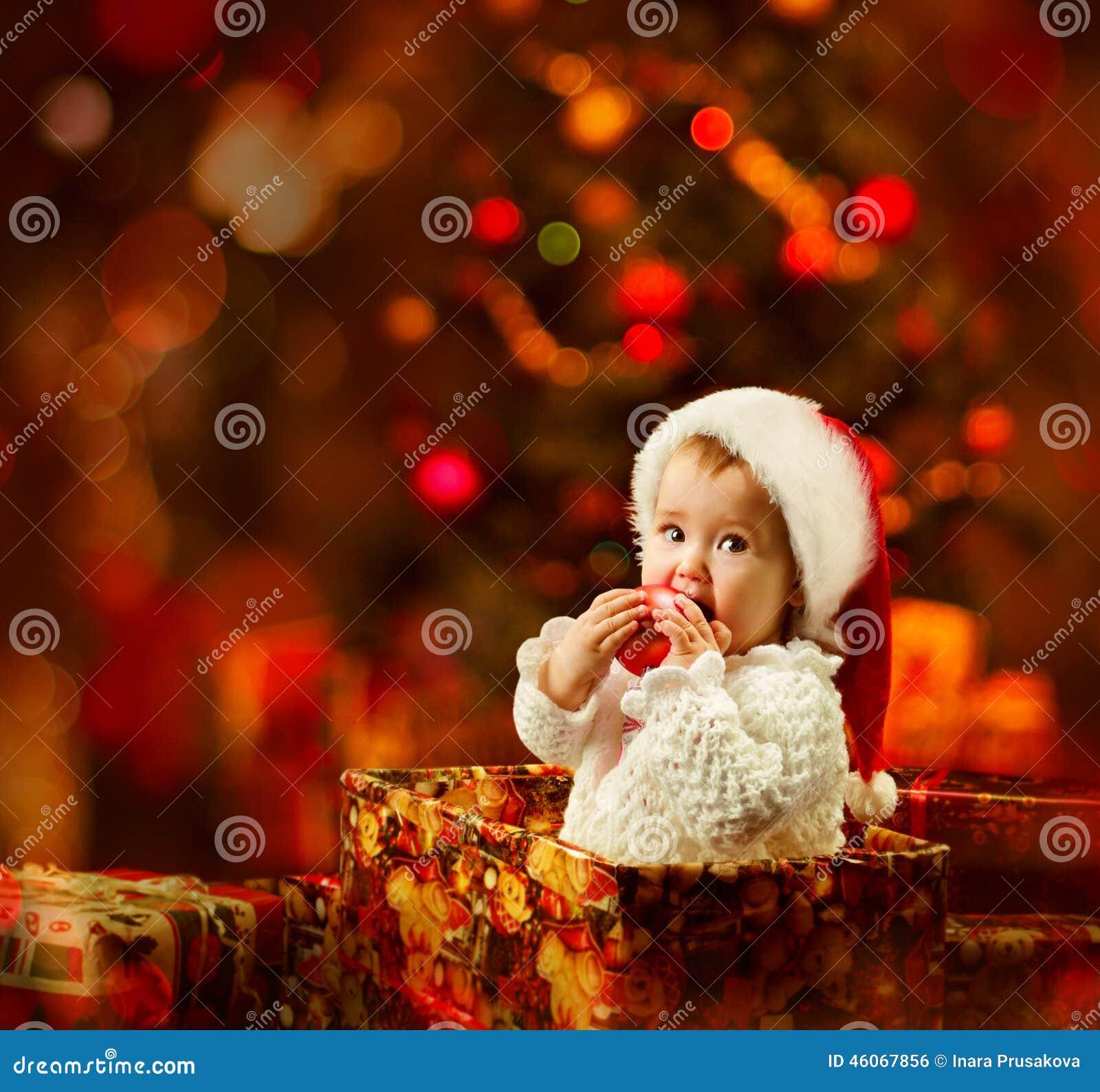 Μωρό Χριστουγέννων στο καπέλο Santa που κρατά την κόκκινη σφαίρα στο παρόν δώρο
