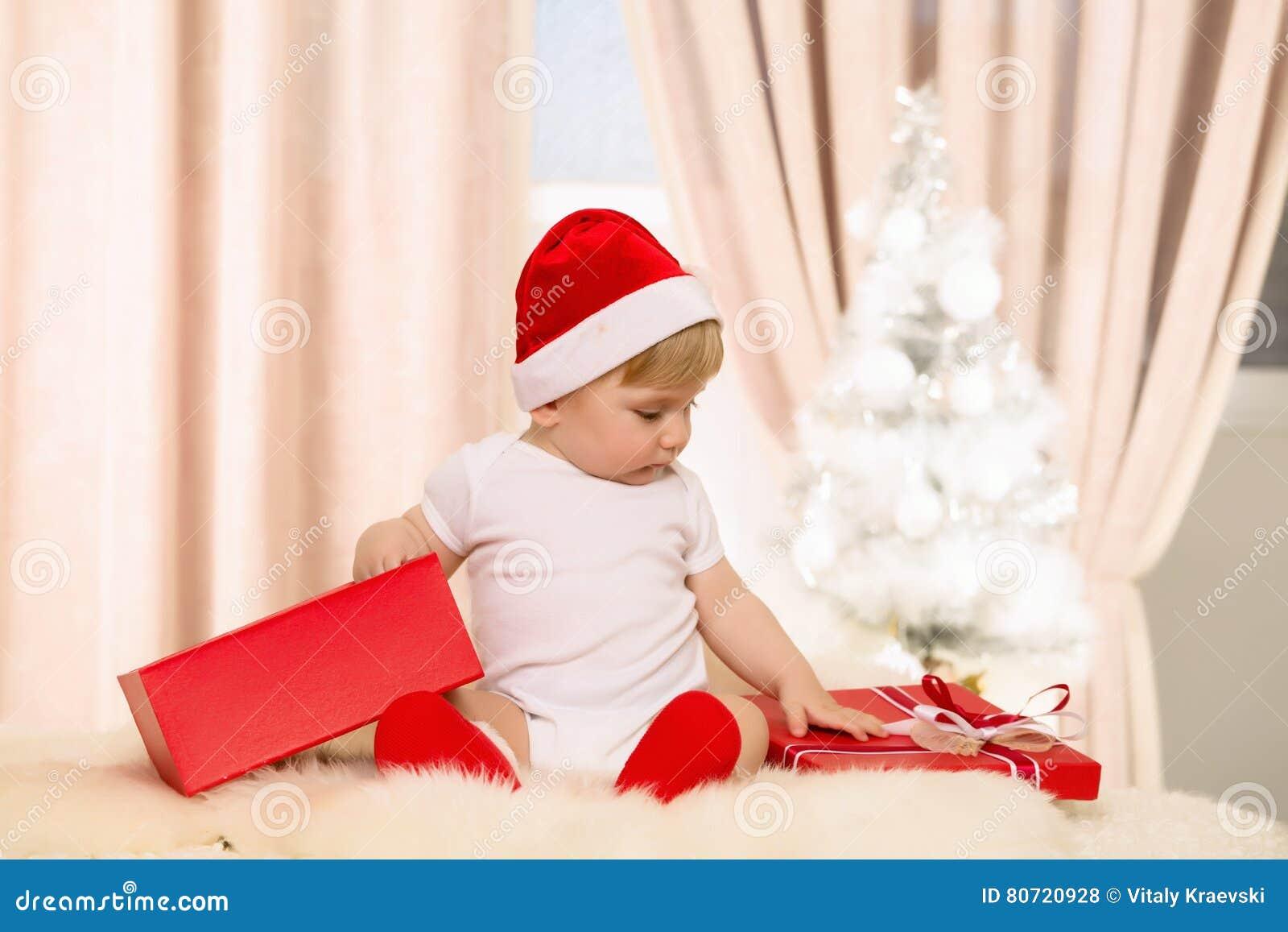 Μωρό Santa που ανοίγει ένα μεγάλο κόκκινο κιβώτιο δώρων