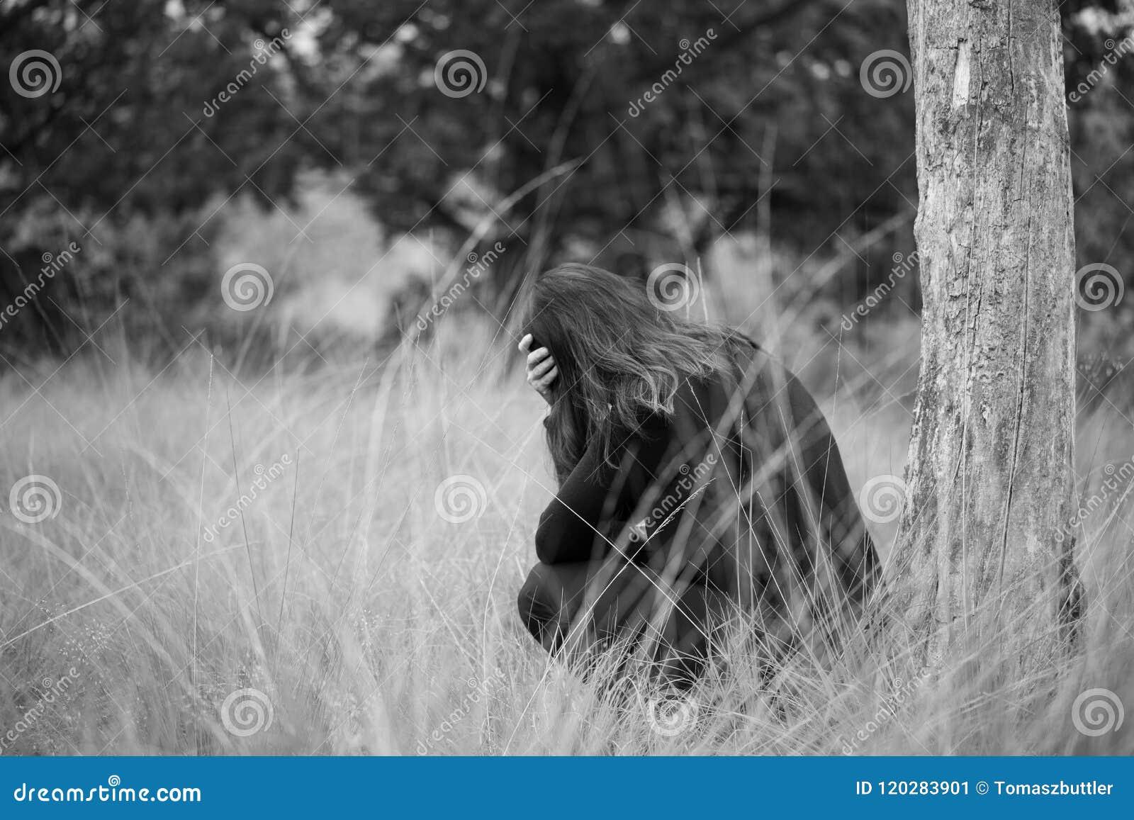 Μόνη νέα καταθλιπτική λυπημένη συνεδρίαση γυναικών κάτω από ένα δέντρο με τα όπλα που διασχίζονται μπροστά από το πρόσωπό της μον
