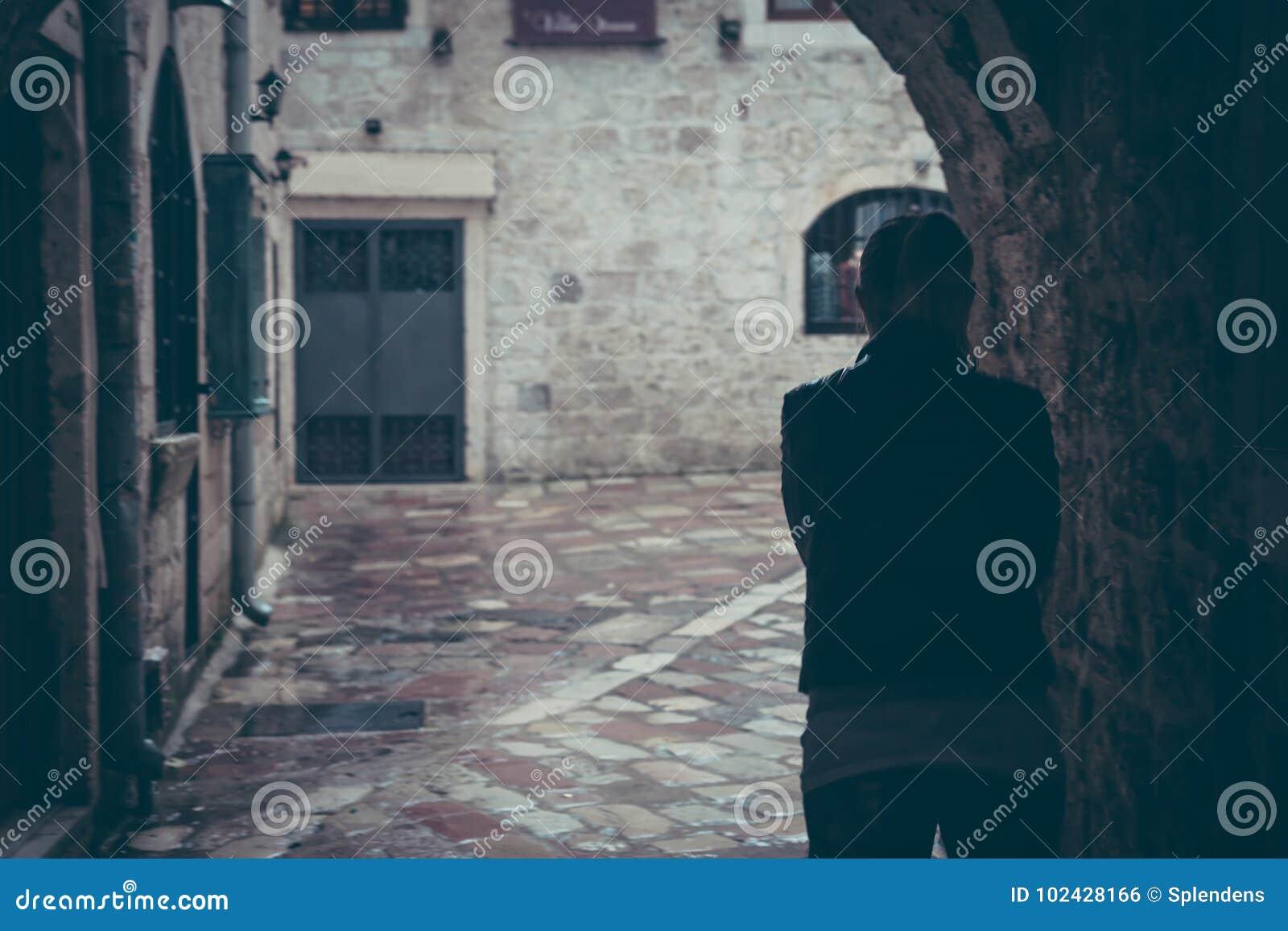 Μόνη σκιαγραφία γυναικών που περπατά μέσω της σκοτεινής σήραγγας της οδού στη βροχερή ημέρα στην παλαιά πόλη κατά τη διάρκεια της