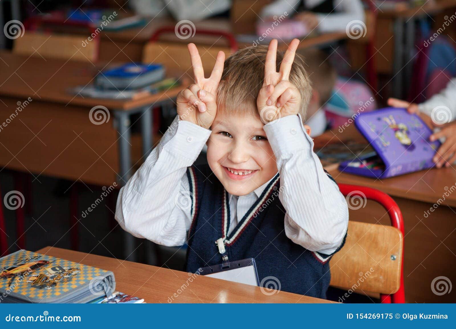 Μόσχα, Ρωσία, το Σεπτέμβριο του 2012 Αλλαγή στο δημοτικό σχολείο Το αγόρι στη σχολική στολή χαμογελά και χτίζει τα πρόσωπα Φωτειν