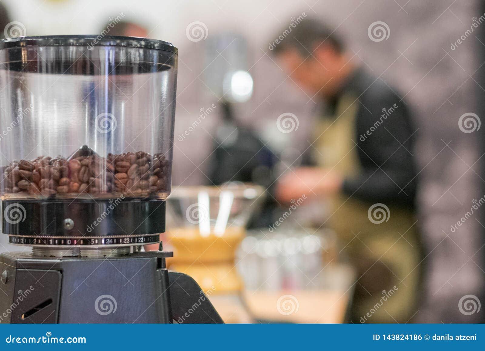 Μύλος καφέ με το θολωμένο μπάρμαν στο υπόβαθρο