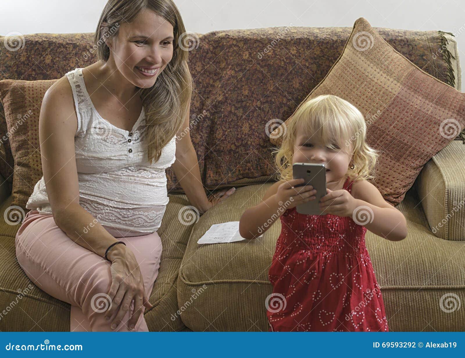 Νέα έγκυος μητέρα που εξετάζει την πληρωμή κορών με το cellul