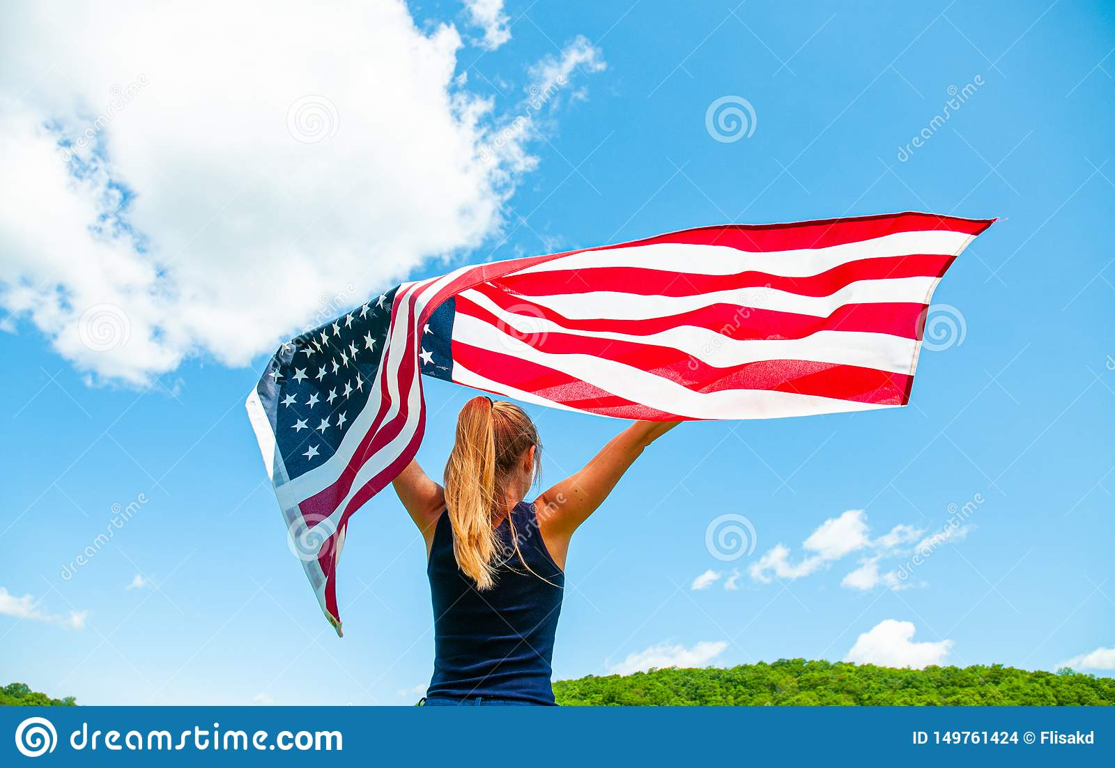Νέα αμερικανική σημαία εκμετάλλευσης γυναικών στο υπόβαθρο μπλε ουρανού Οι Ηνωμένες Πολιτείες γιορτάζουν 4ος του Ιουλίου