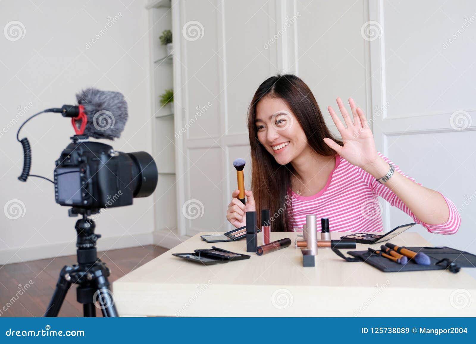 Νέα ασιατική ομορφιά γυναικών blogger που επιδεικνύει πώς να αποτελέσει το τηλεοπτικό TU