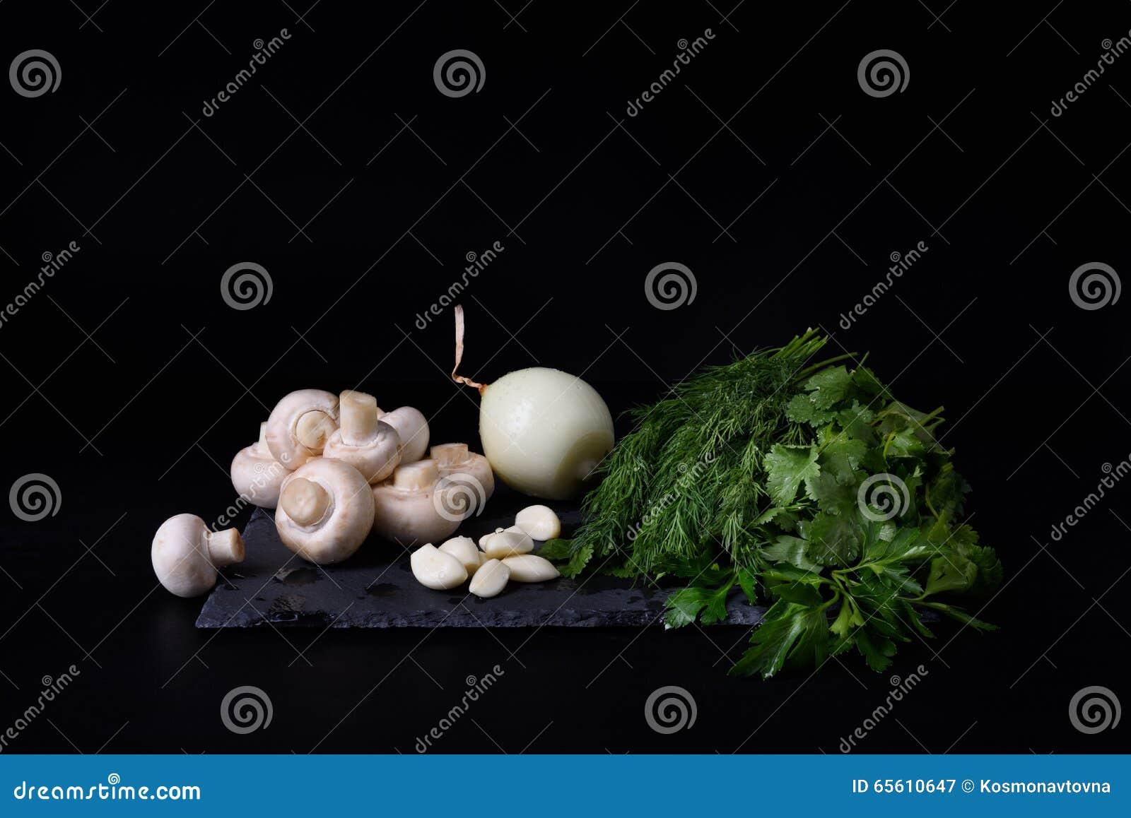 Νέα λαχανικά άνοιξη στον πίνακα πλακών, μαύρο υπόβαθρο Champignons, άνηθος, σκόρδο, κρεμμύδι