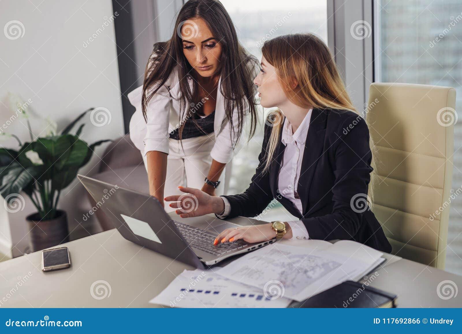 Νέα γυναίκα βοηθός που συσκέπτεται με έναν τοπ διευθυντή που παρουσιάζει στοιχεία όσον αφορά την οθόνη lap-top και που ζητά τη συ