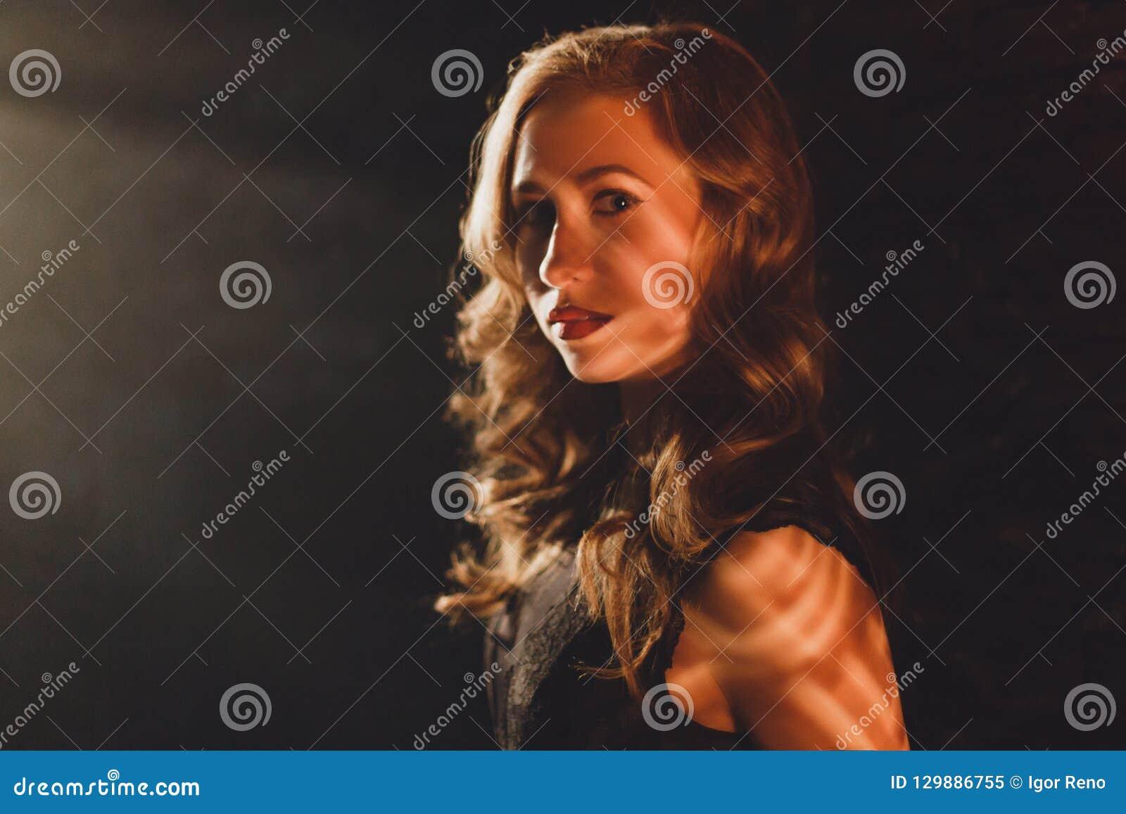 Νέα γυναίκα γοητείας που στέκεται στην ακτίνα ελαφριού και που φαίνεται κεκλεισμένων των θυρών