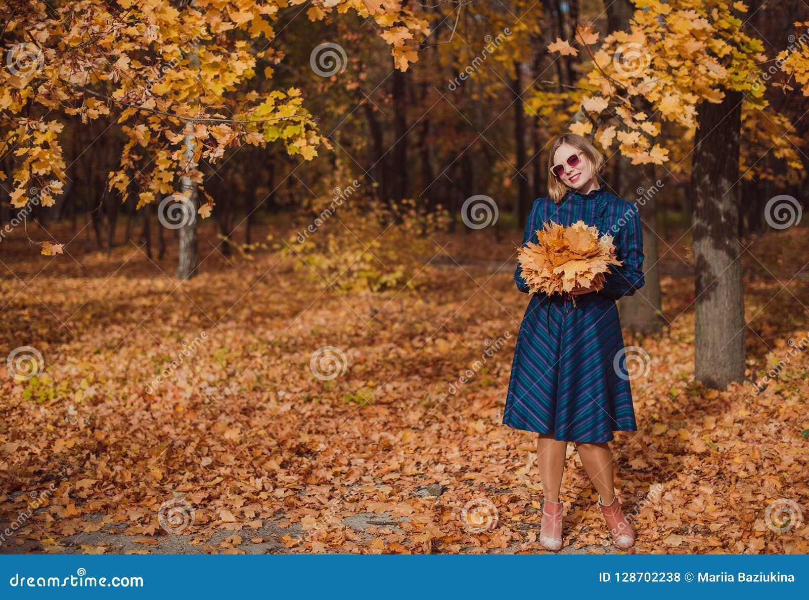 Νέα γυναίκα με τα ξανθά μαλλιά που φορούν το μπλε φόρεμα που περπατά στο πάρκο φθινοπώρου