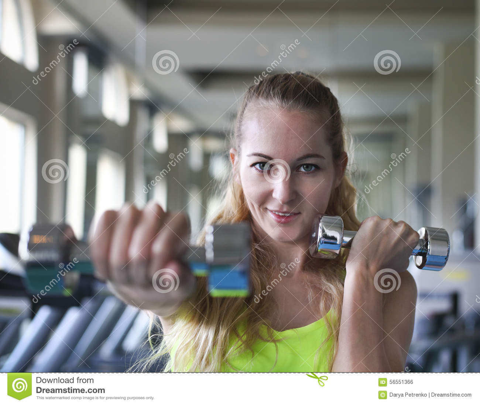 Download Νέα γυναίκα με τα Barbells στο υπόβαθρο γυμναστικής Στοκ Εικόνες - εικόνα από μυς, ικανότητα: 56551366