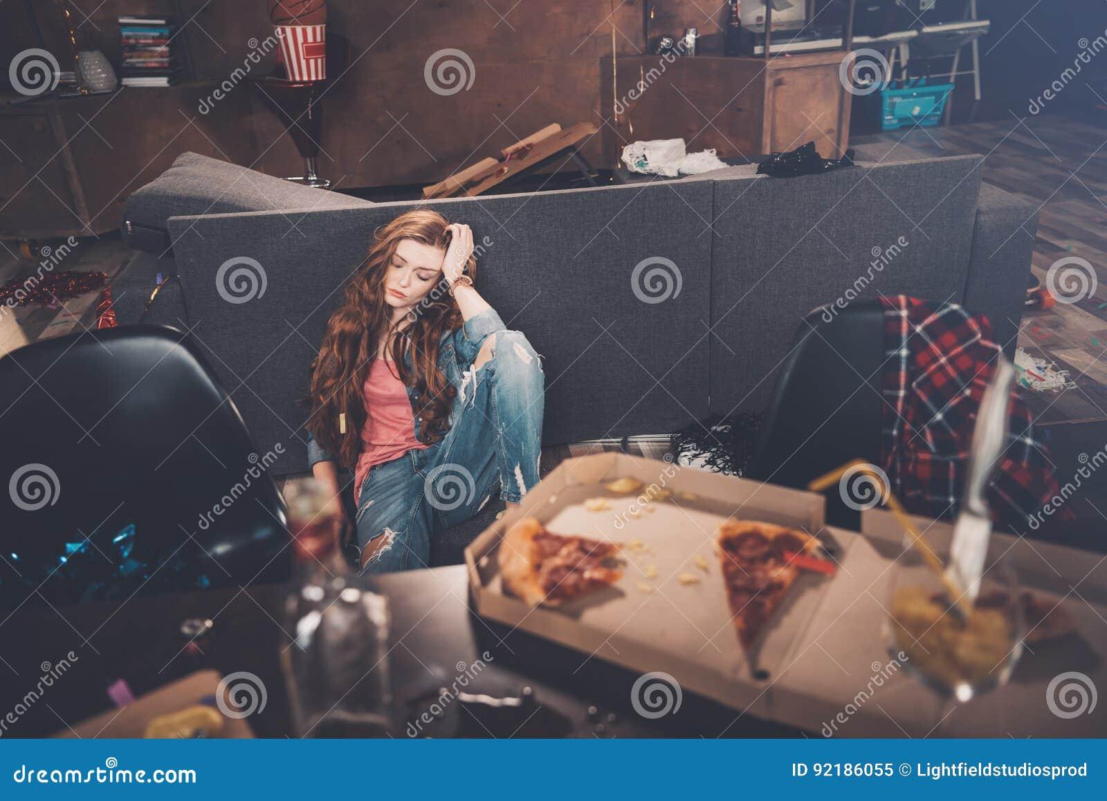 Νέα γυναίκα με τις ιδιαίτερες προσοχές που κάθεται στο πάτωμα στο ακατάστατο δωμάτιο μετά από το κόμμα
