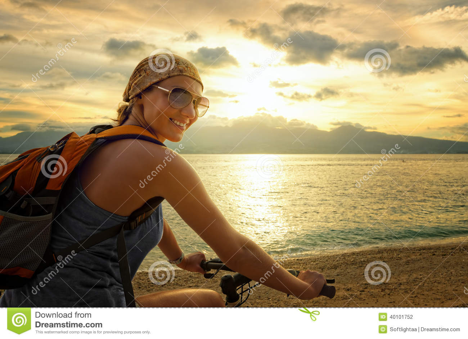 Νέα γυναίκα με το σακίδιο πλάτης που στέκεται στην ακτή κοντά στο ποδήλατό του