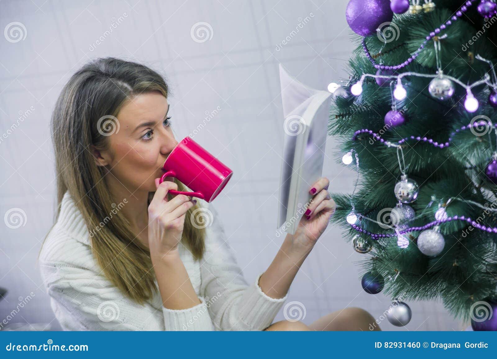 Νέα γυναίκα με το φλυτζάνι της καυτής σοκολάτας μπροστά από το χριστουγεννιάτικο δέντρο