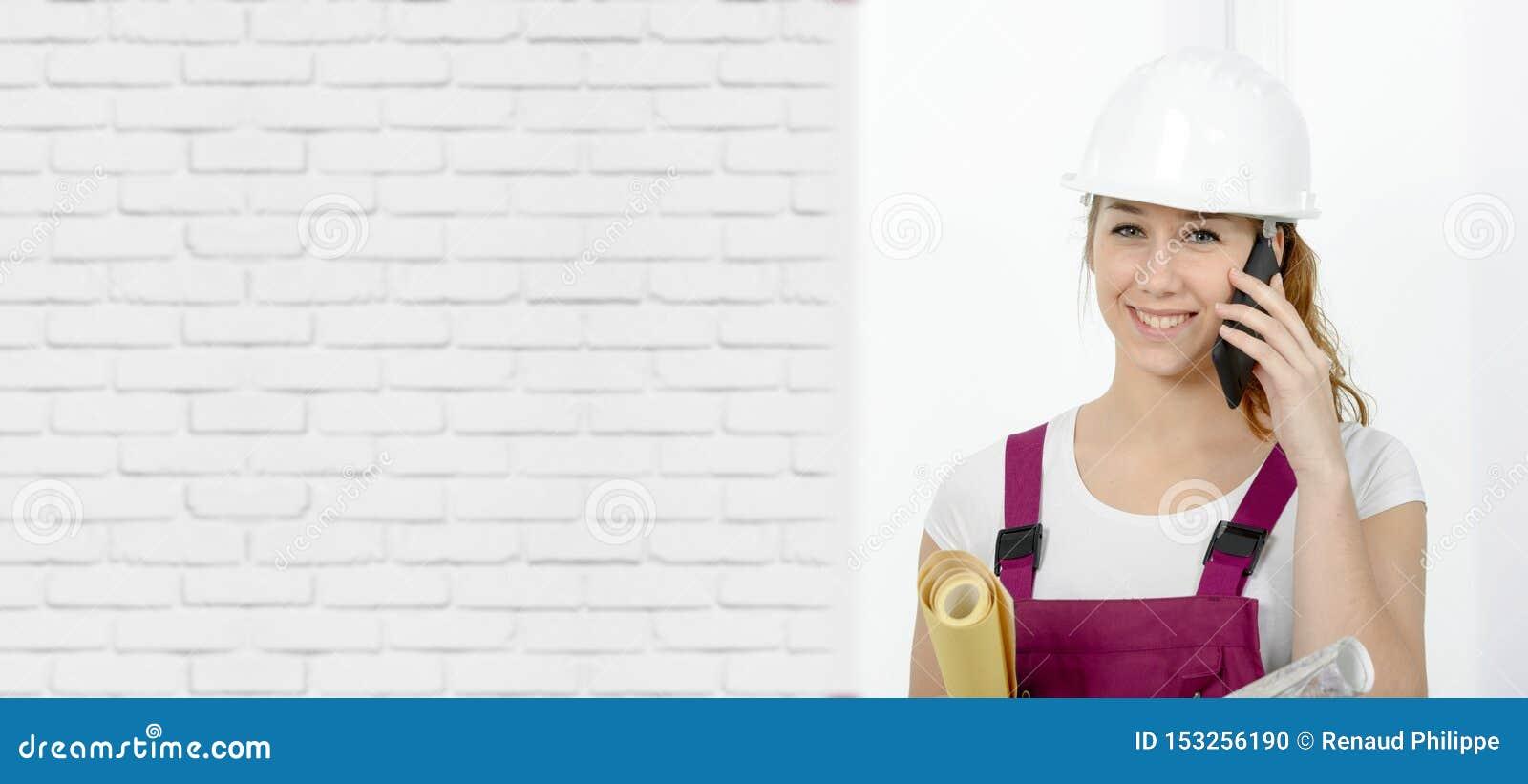 Νέα γυναίκα μηχανικών με το σκληρό καπέλο ασφάλειας που μιλά στο τηλέφωνο