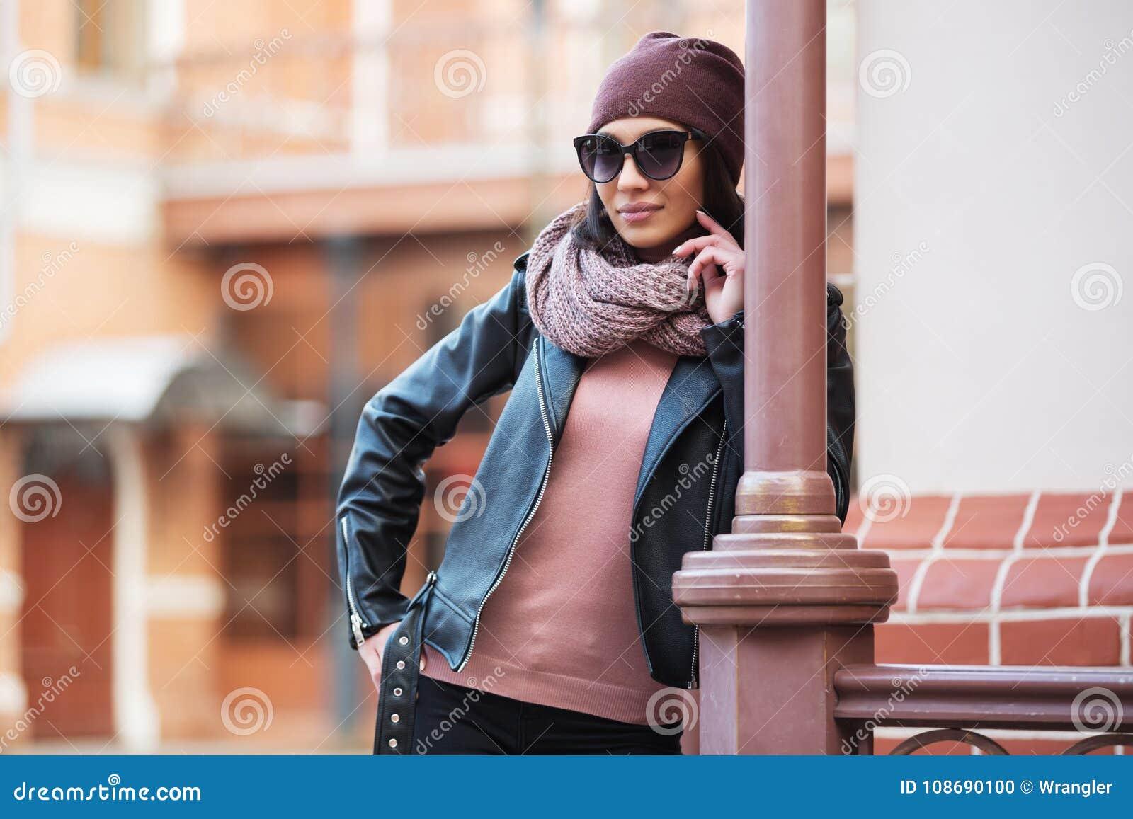 Νέα γυναίκα μόδας στο μαύρο σακάκι δέρματος που κλίνει στο κιγκλίδωμα