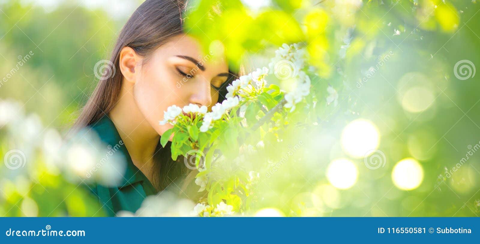 Νέα γυναίκα ομορφιάς που απολαμβάνει τον οπωρώνα μήλων φύσης την άνοιξη, ευτυχές όμορφο κορίτσι σε έναν κήπο με τα ανθίζοντας οπω