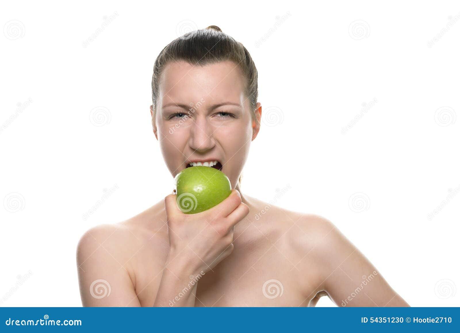 Νέα γυναίκα που δαγκώνει τη φρέσκια πράσινη Apple ενάντια στο λευκό