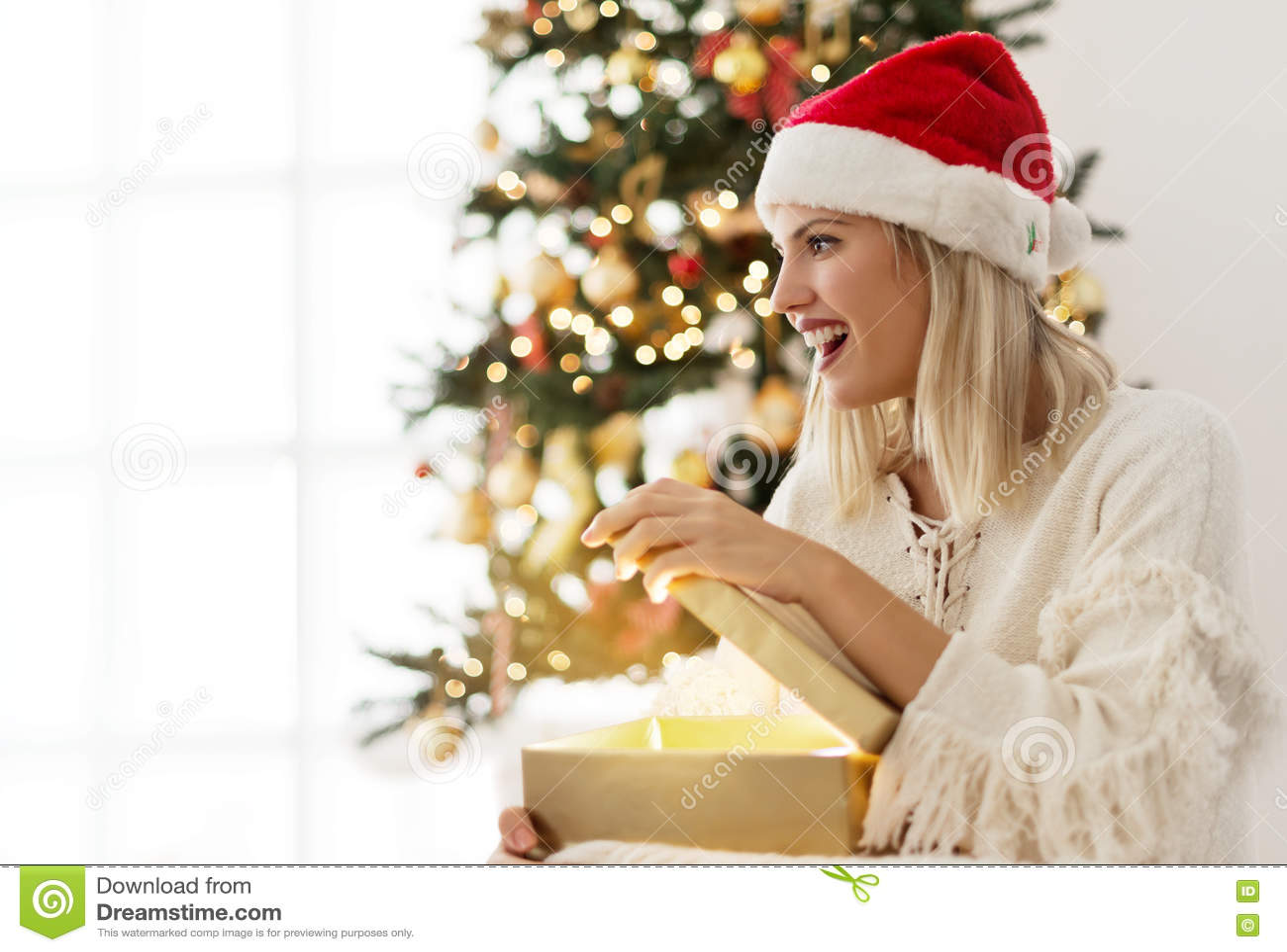Νέα γυναίκα που ανοίγει ένα παρόν στο πρωί Χριστουγέννων