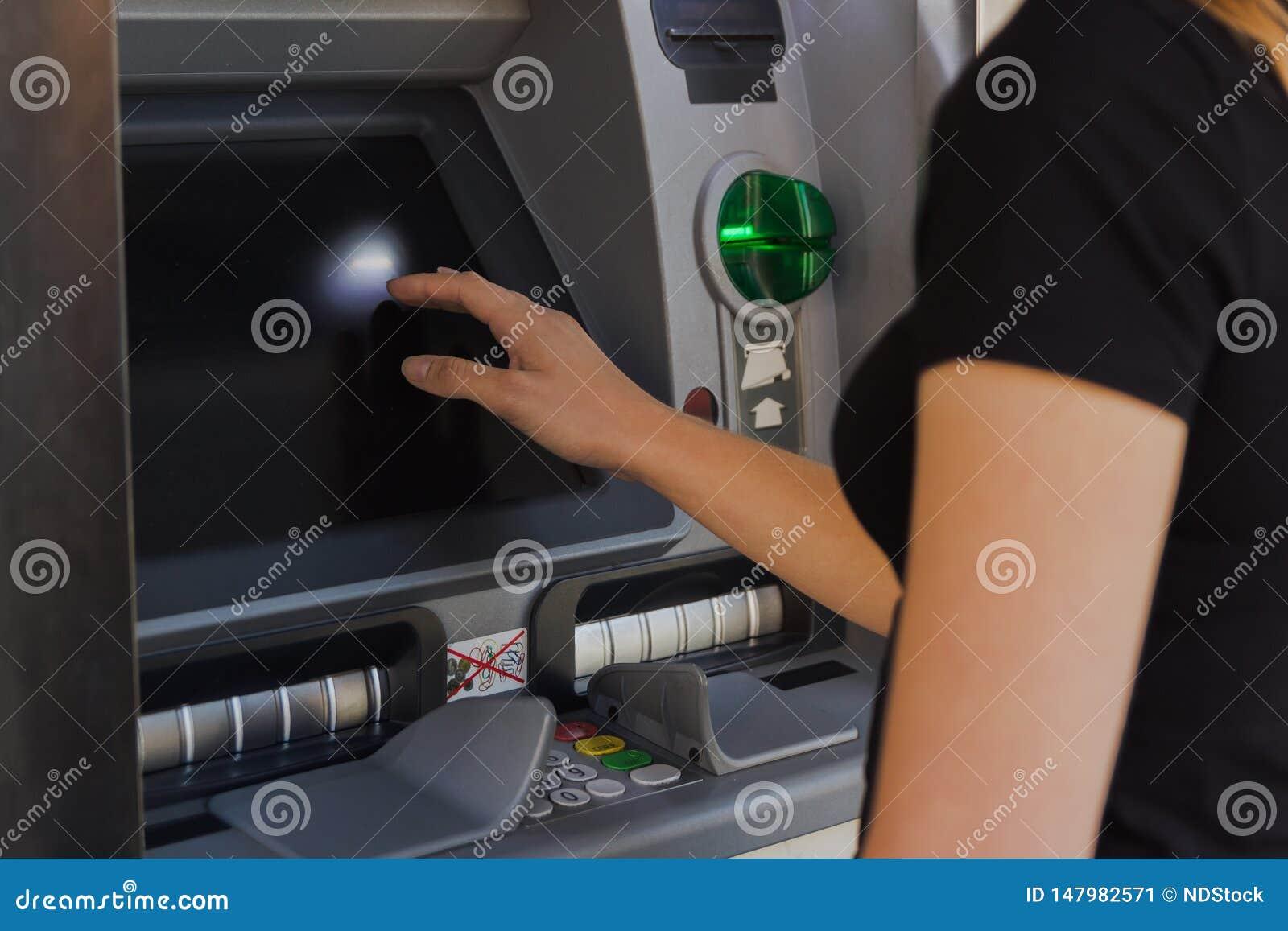 Νέα γυναίκα που αποσύρει τα μετρητά από μια μηχανή μετρητών