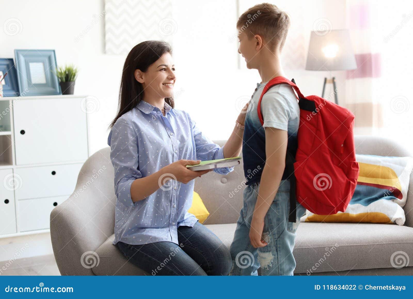 Νέα γυναίκα που βοηθά την λίγο παιδί να πάρει έτοιμη για το σχολείο