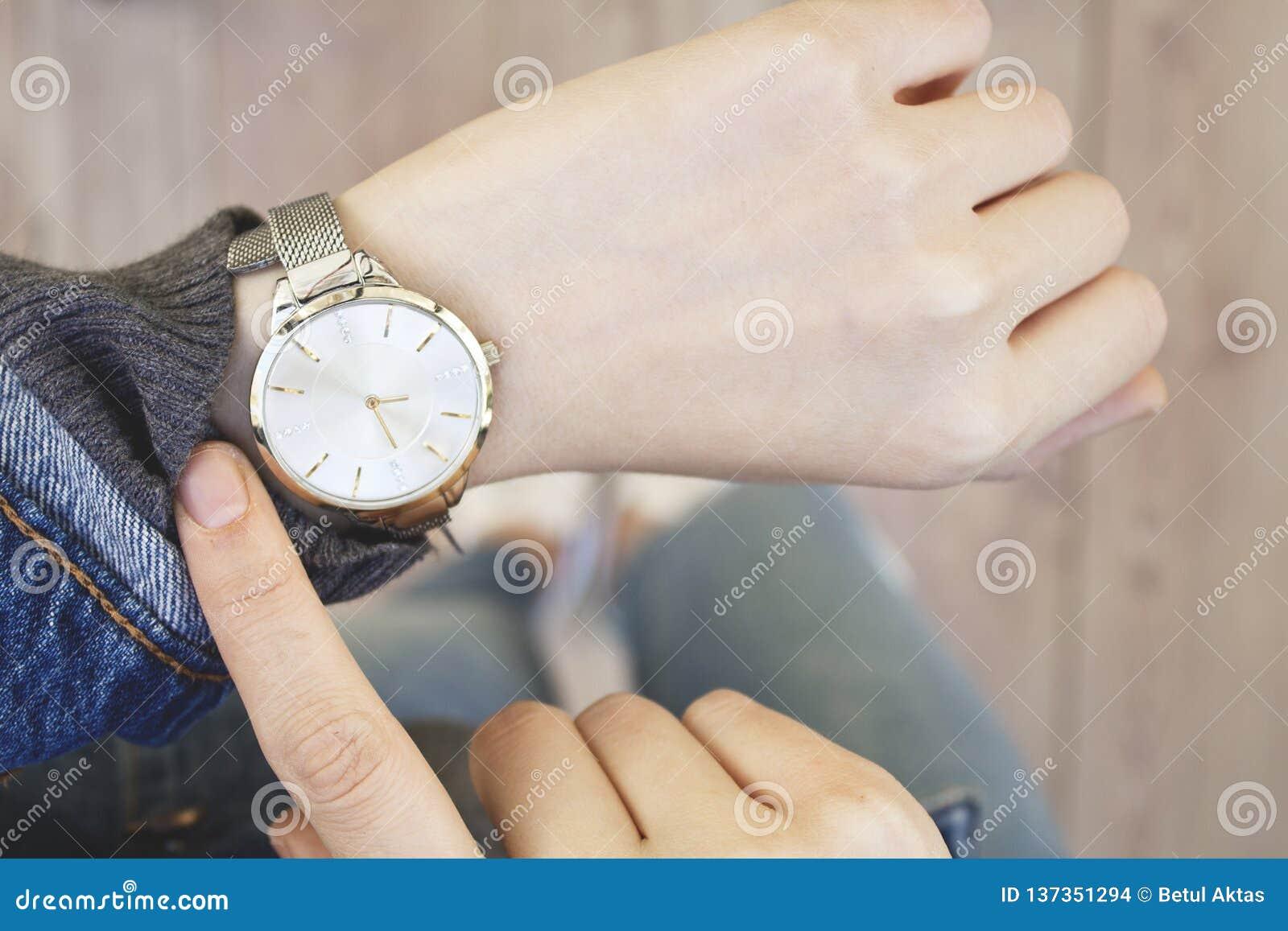 Νέα γυναίκα που ελέγχει το χρόνο το ρολόι της
