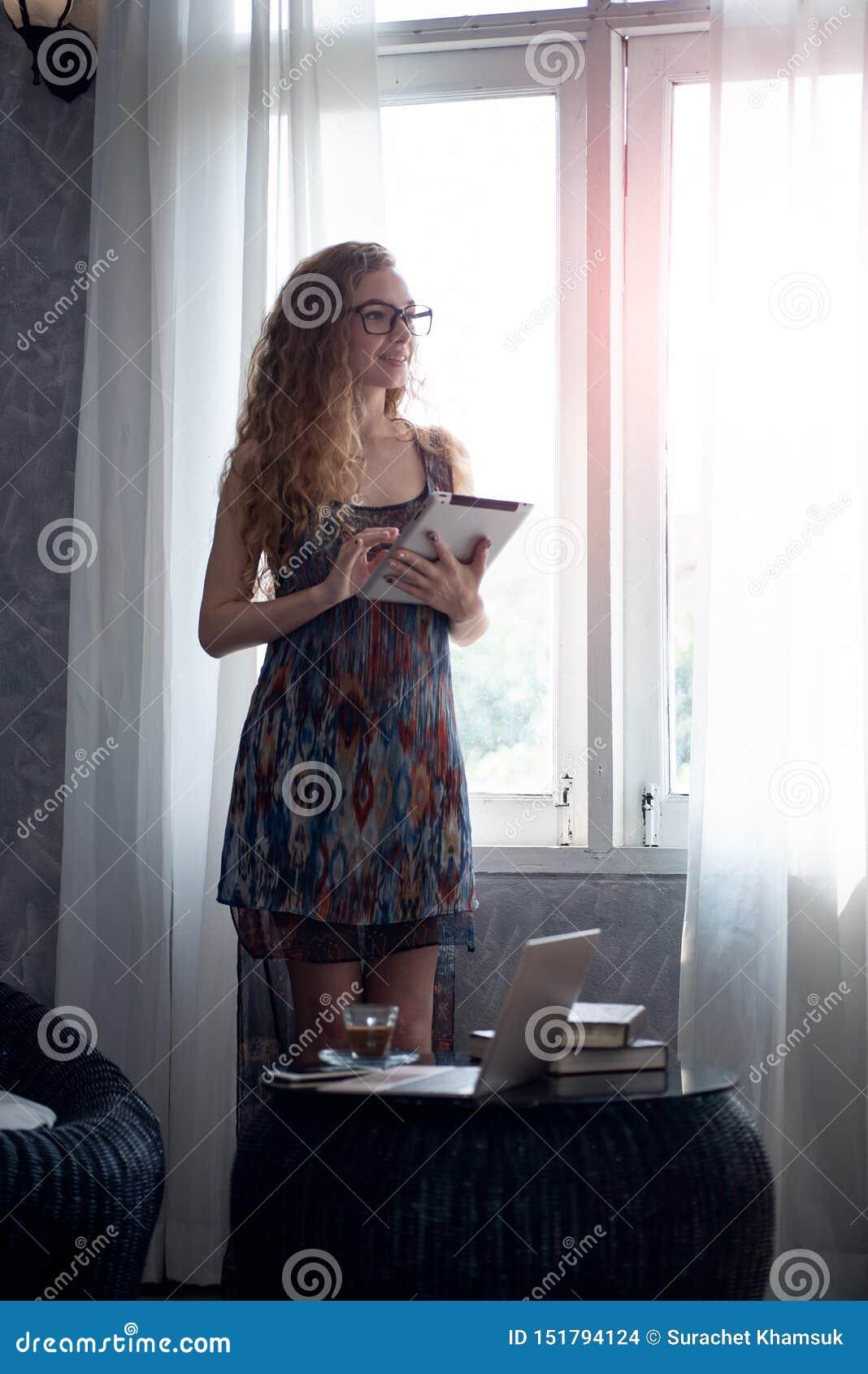 Νέα γυναίκα που εργάζεται στον ψηφιακό υπολογιστή ταμπλετών στο σπίτι