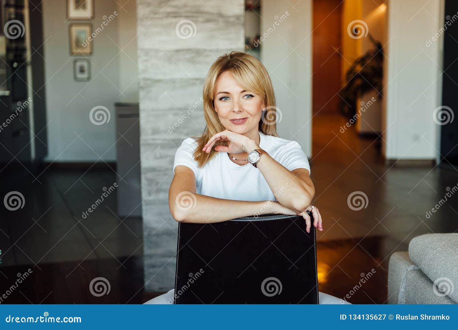 Νέα γυναίκα που κάθεται στο σπίτι στη σύγχρονη καρέκλα κοντά στη χαλάρωση παραθύρων στο καθιστικό
