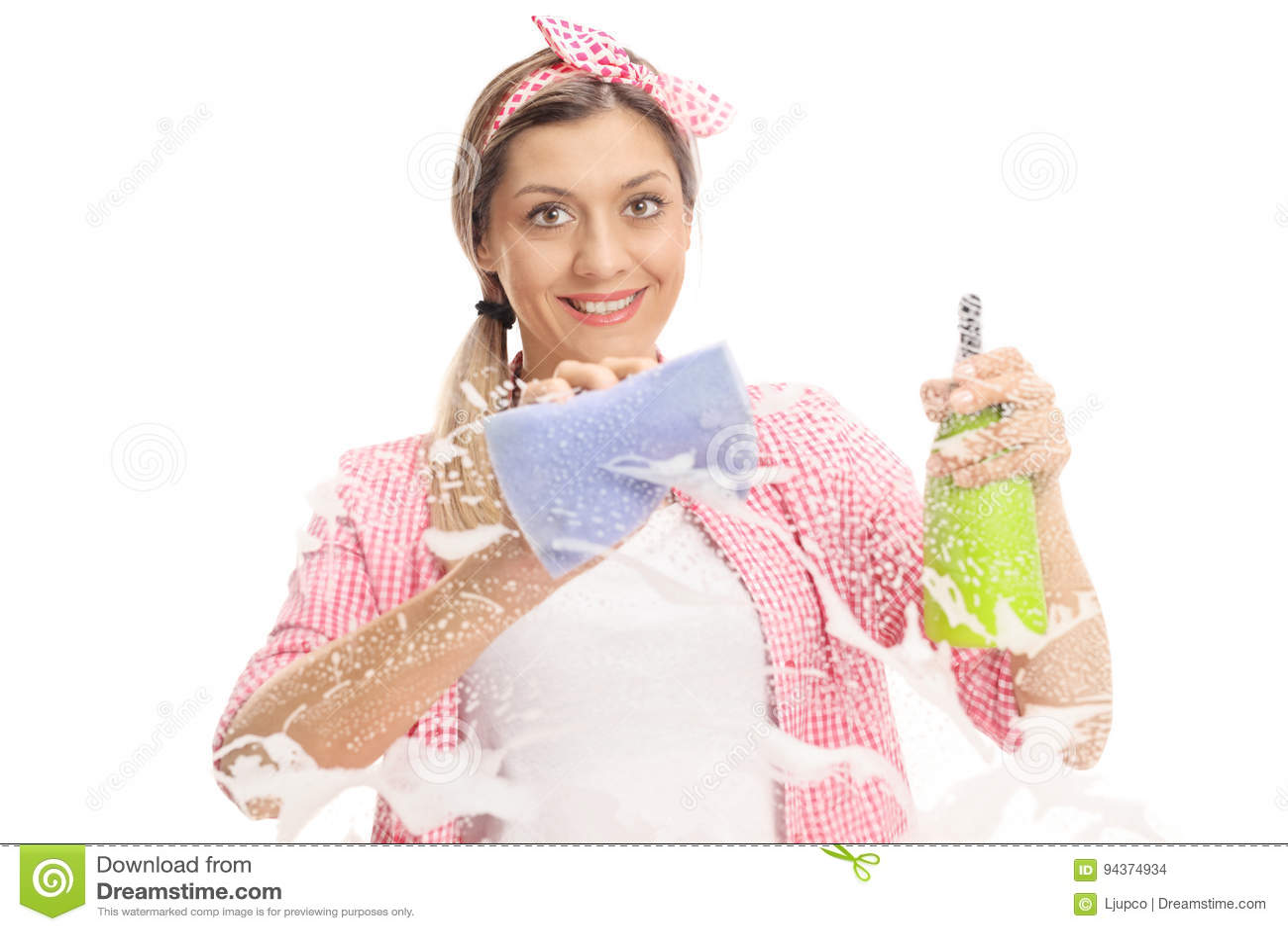 Νέα γυναίκα που καθαρίζει ένα παράθυρο με την πετσέτα και το απορρυπαντικό