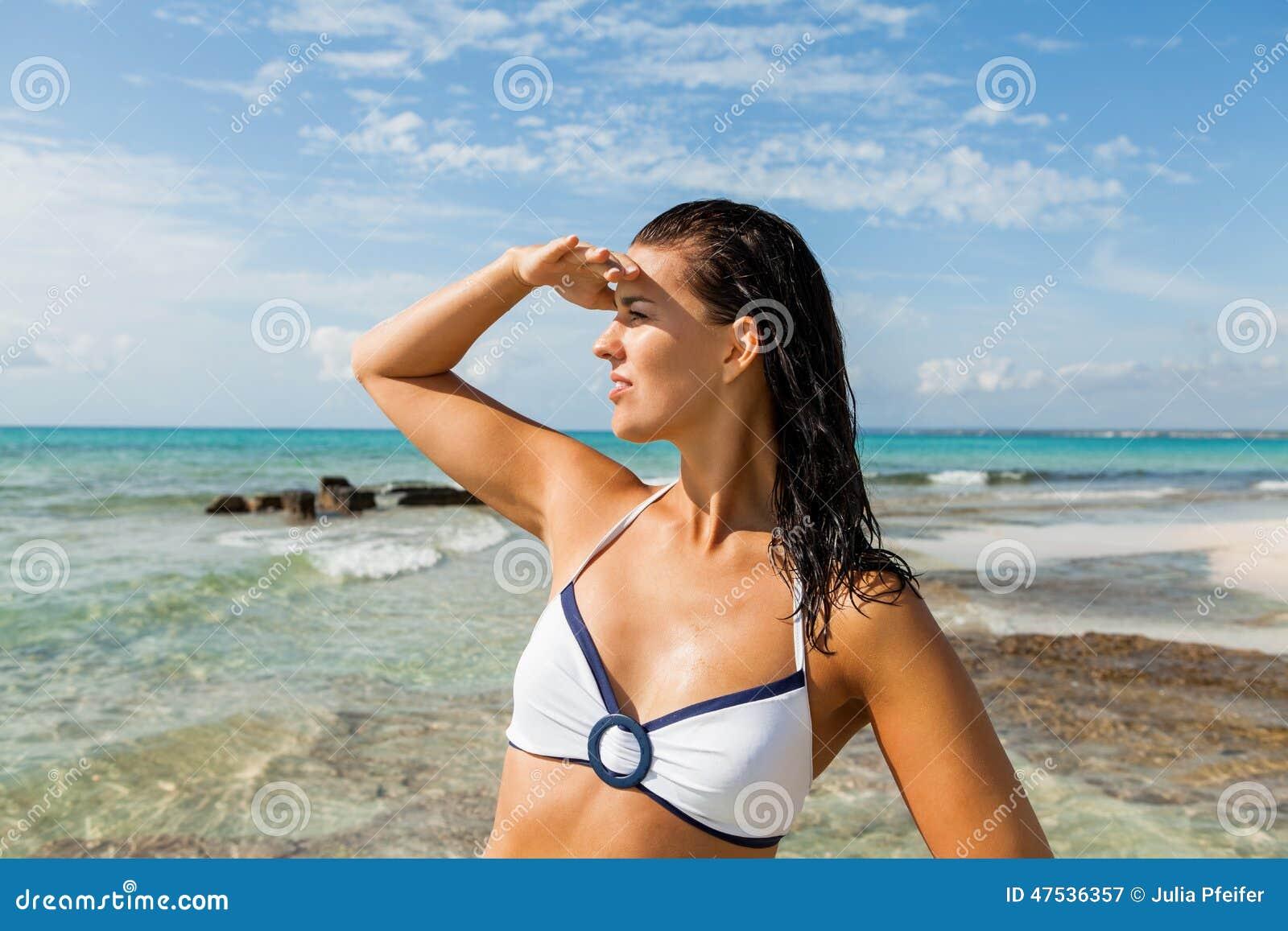 Νέα γυναίκα που κοιτάζει μακριά στην παραλία