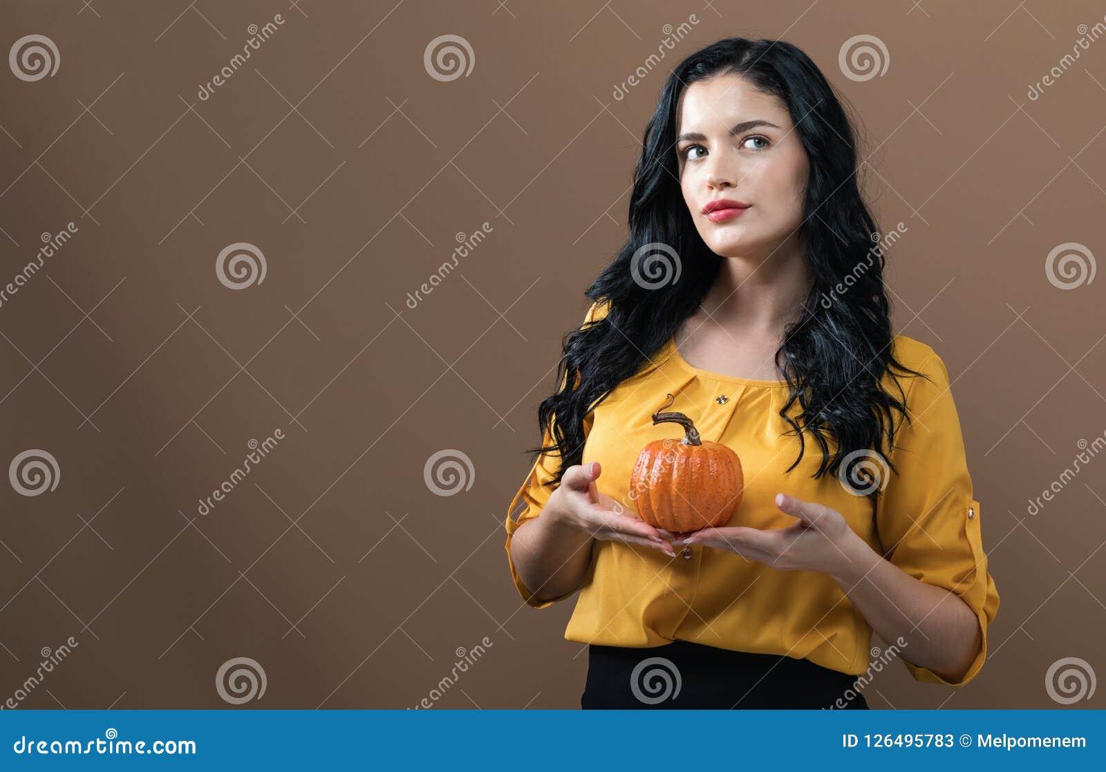 Νέα γυναίκα που κρατά μια κολοκύθα