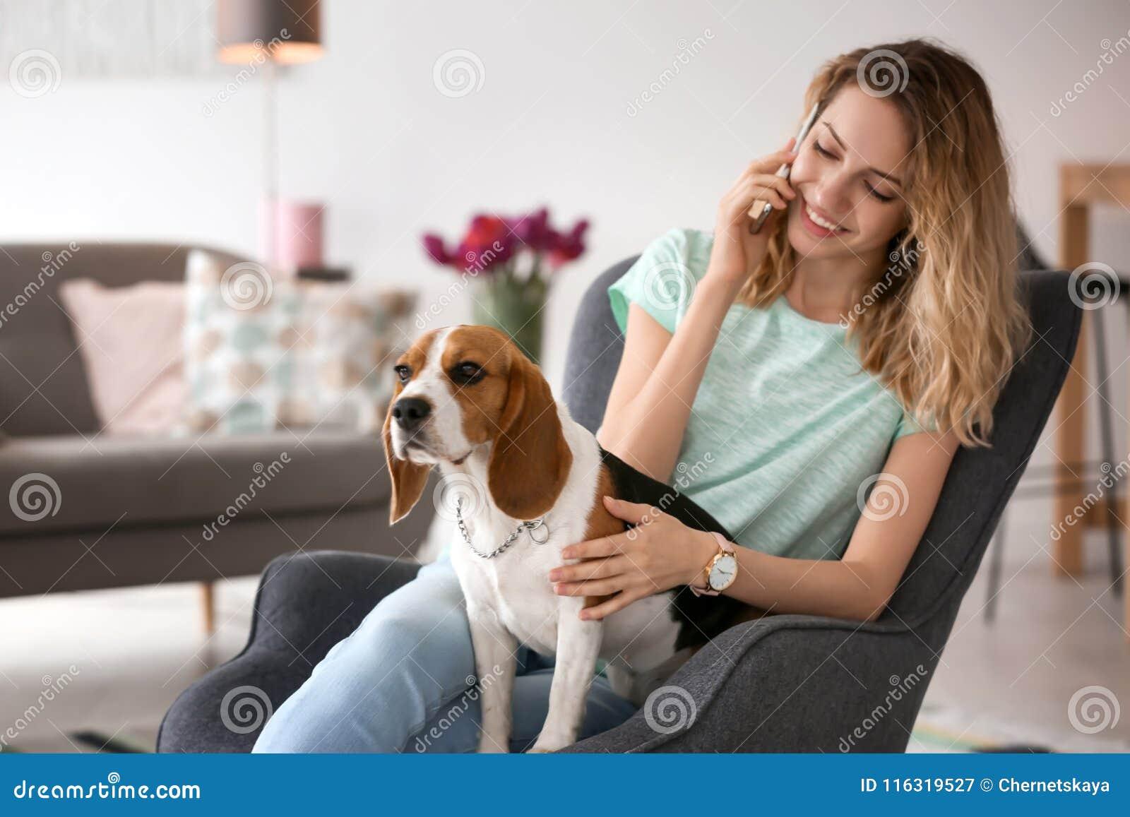 Νέα γυναίκα που μιλά στο τηλέφωνο κτυπώντας το σκυλί της