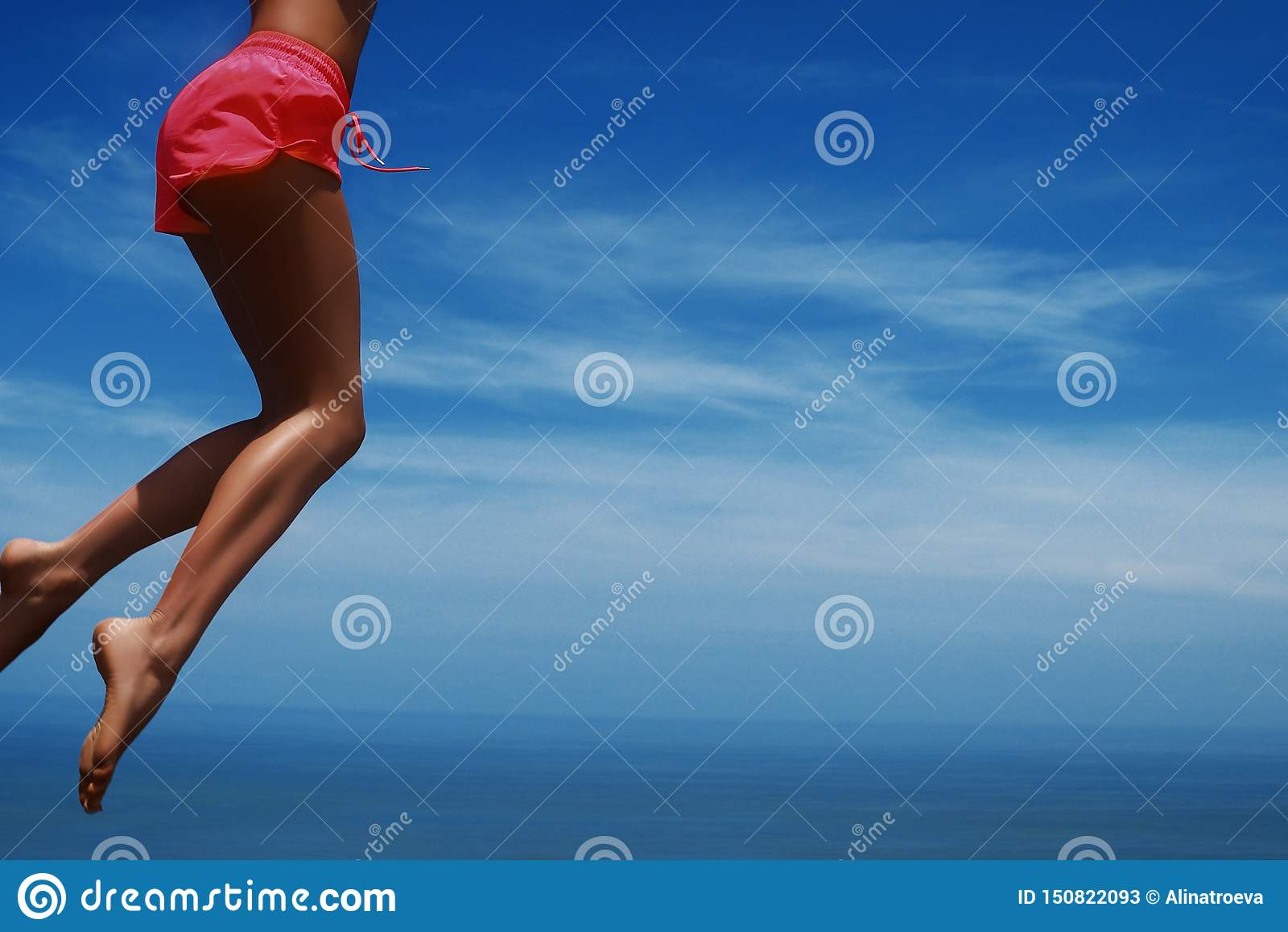 Νέα γυναίκα που πηδά στην τροπική παραλία Μπλε ουρανός και λεπτά πόδια