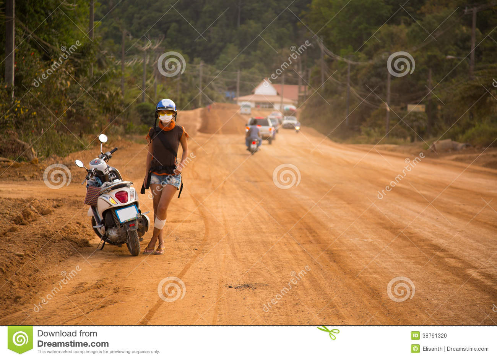 Νέα γυναίκα που στέκεται δίπλα σε μια μοτοσικλέτα