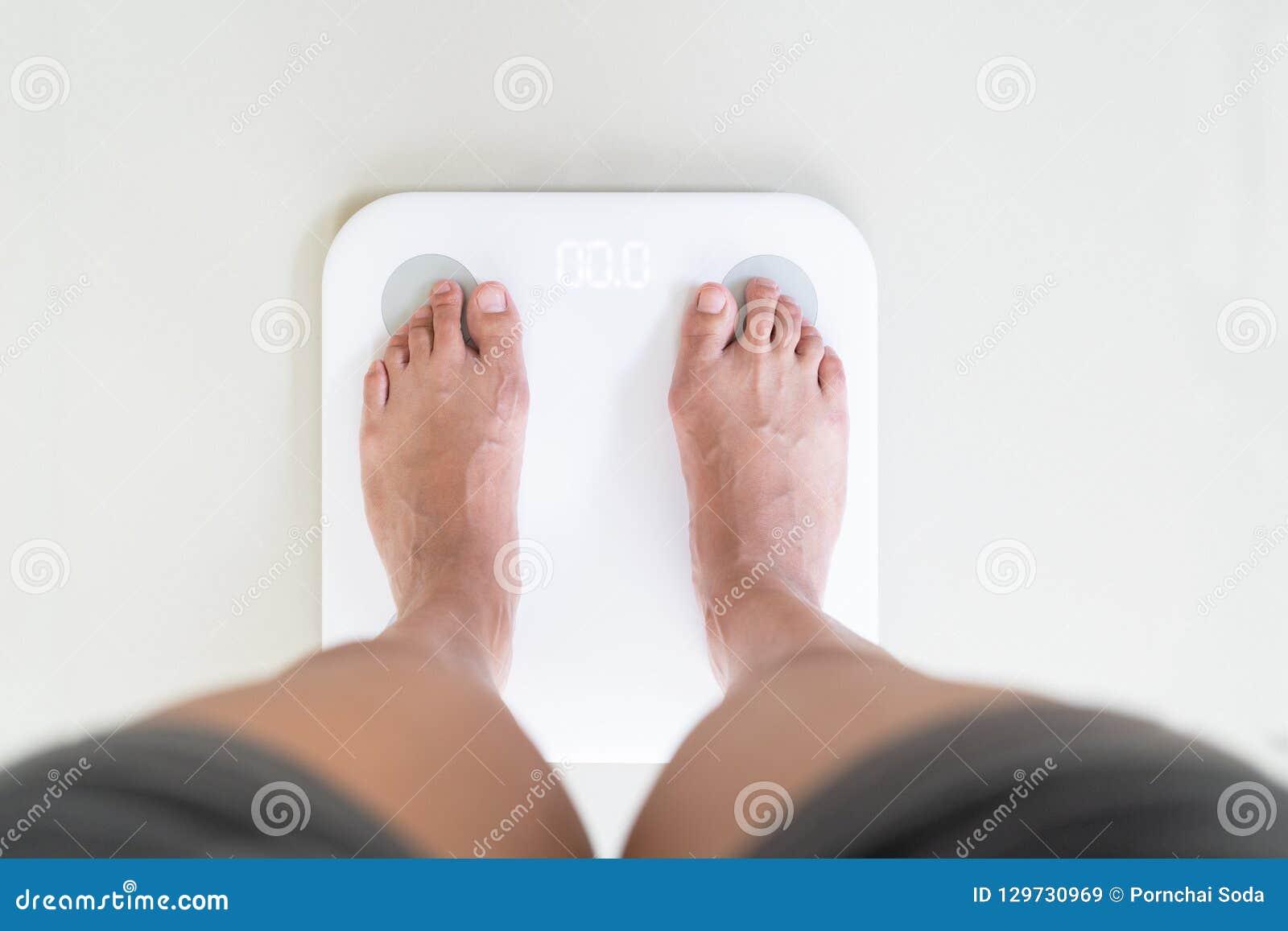 Νέα γυναίκα που στέκεται στην ψηφιακή κλίμακα βάρους