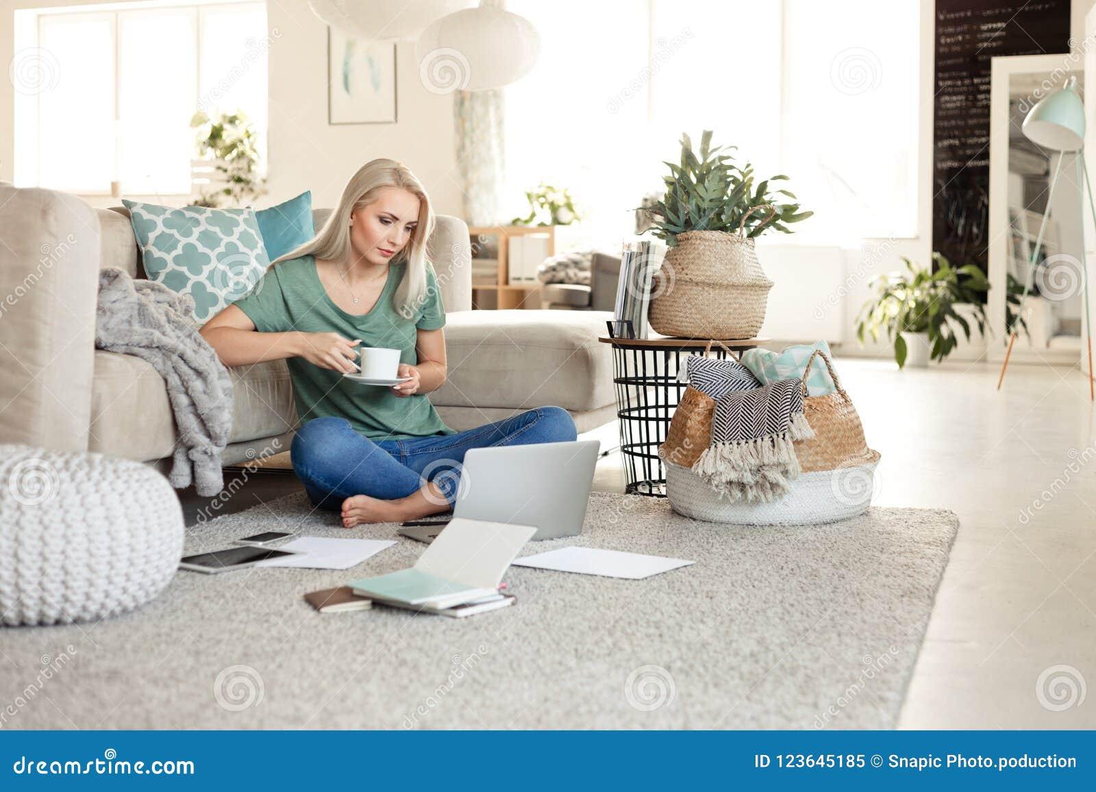 Νέα γυναίκα που στηρίζονται στο σπίτι, καφές κατανάλωσης και χρησιμοποίηση του lap-top