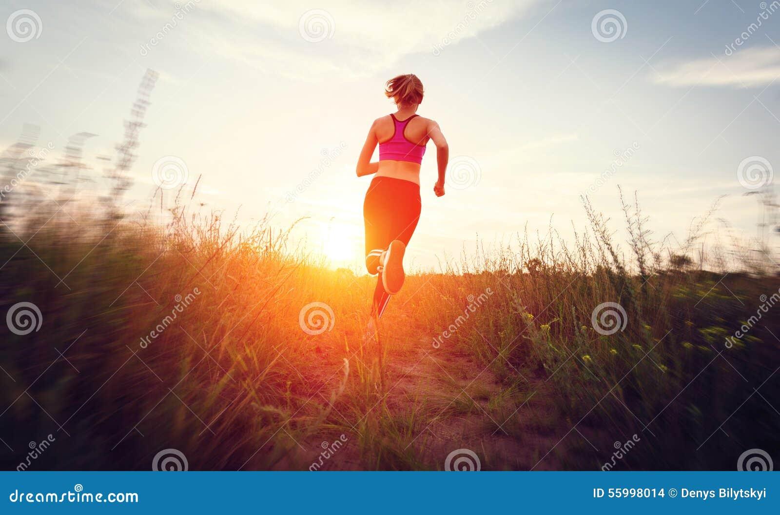 Νέα γυναίκα που τρέχει σε έναν αγροτικό δρόμο στο ηλιοβασίλεμα