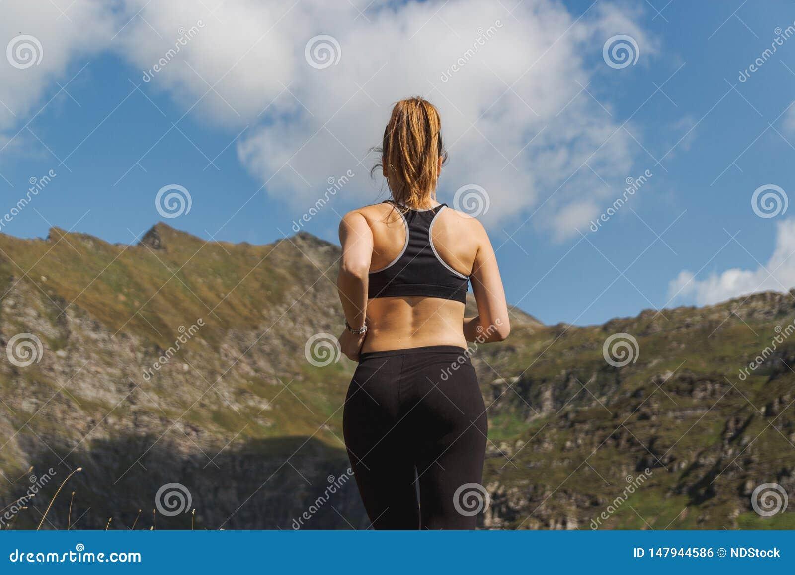 Νέα γυναίκα που τρέχει στα βουνά κατά τη διάρκεια μιας ηλιόλουστης ημέρας