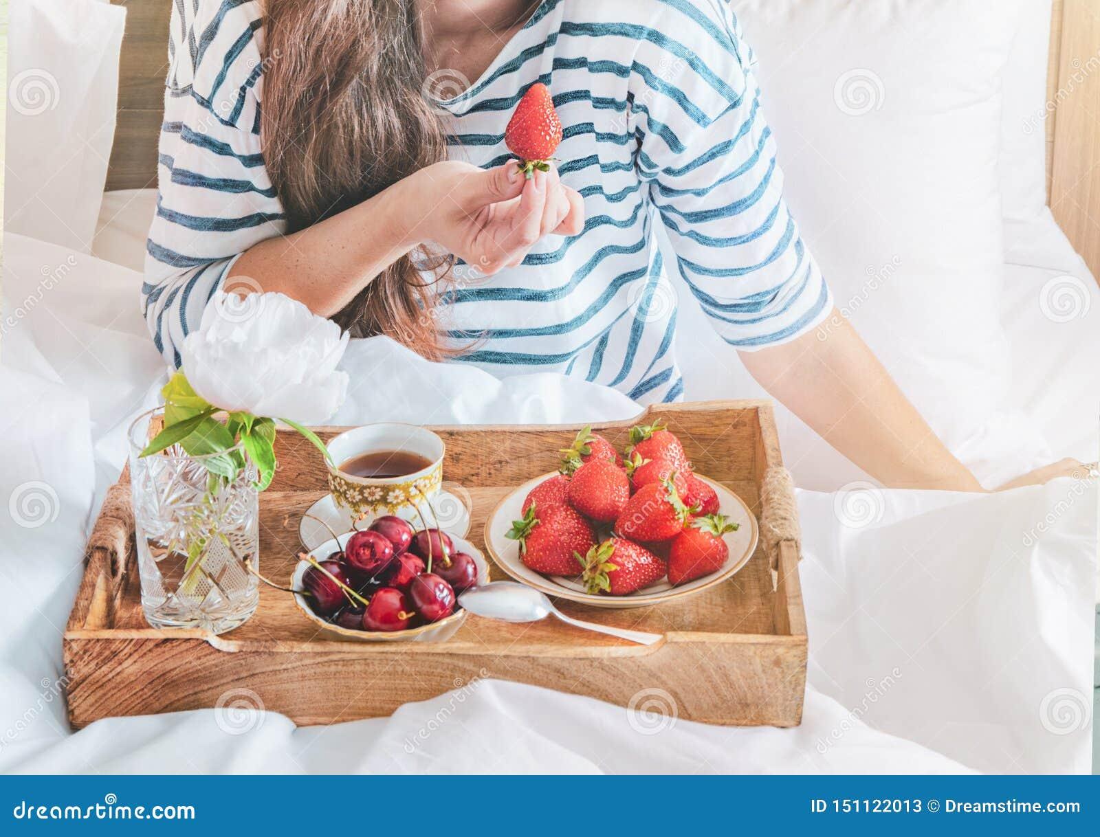 Νέα γυναίκα που τρώει το υγιές πρόγευμα στο κρεβάτι Ρομαντικό πρόγευμα με τις φράουλες και γλυκό κεράσι σε ένα κρεβάτι